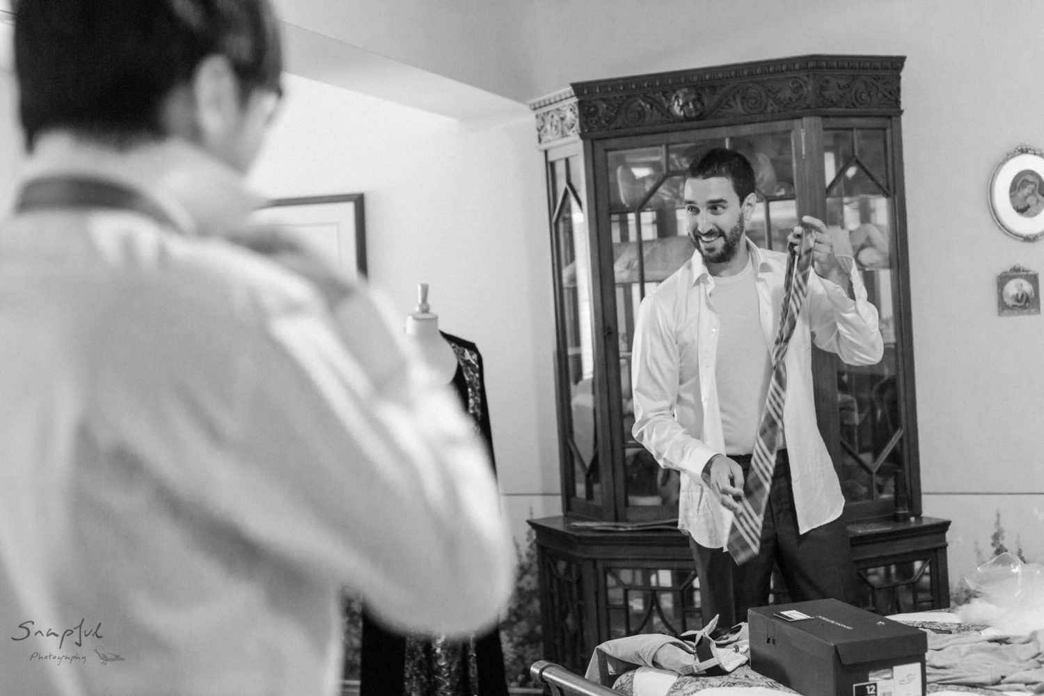 Groom getting ready in front of mirror