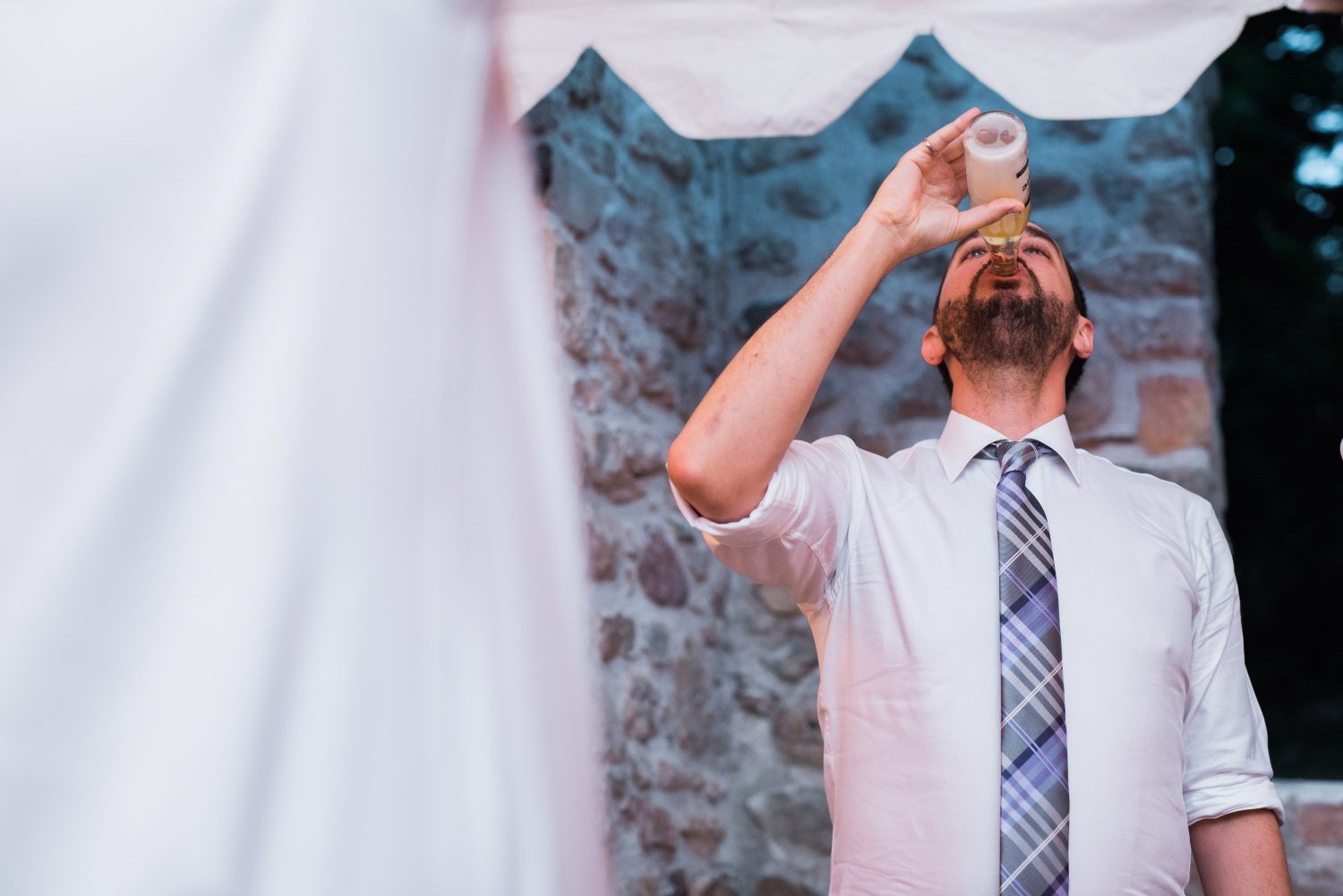 Groom chugs a beer after losing a game at Alton Mill wedding