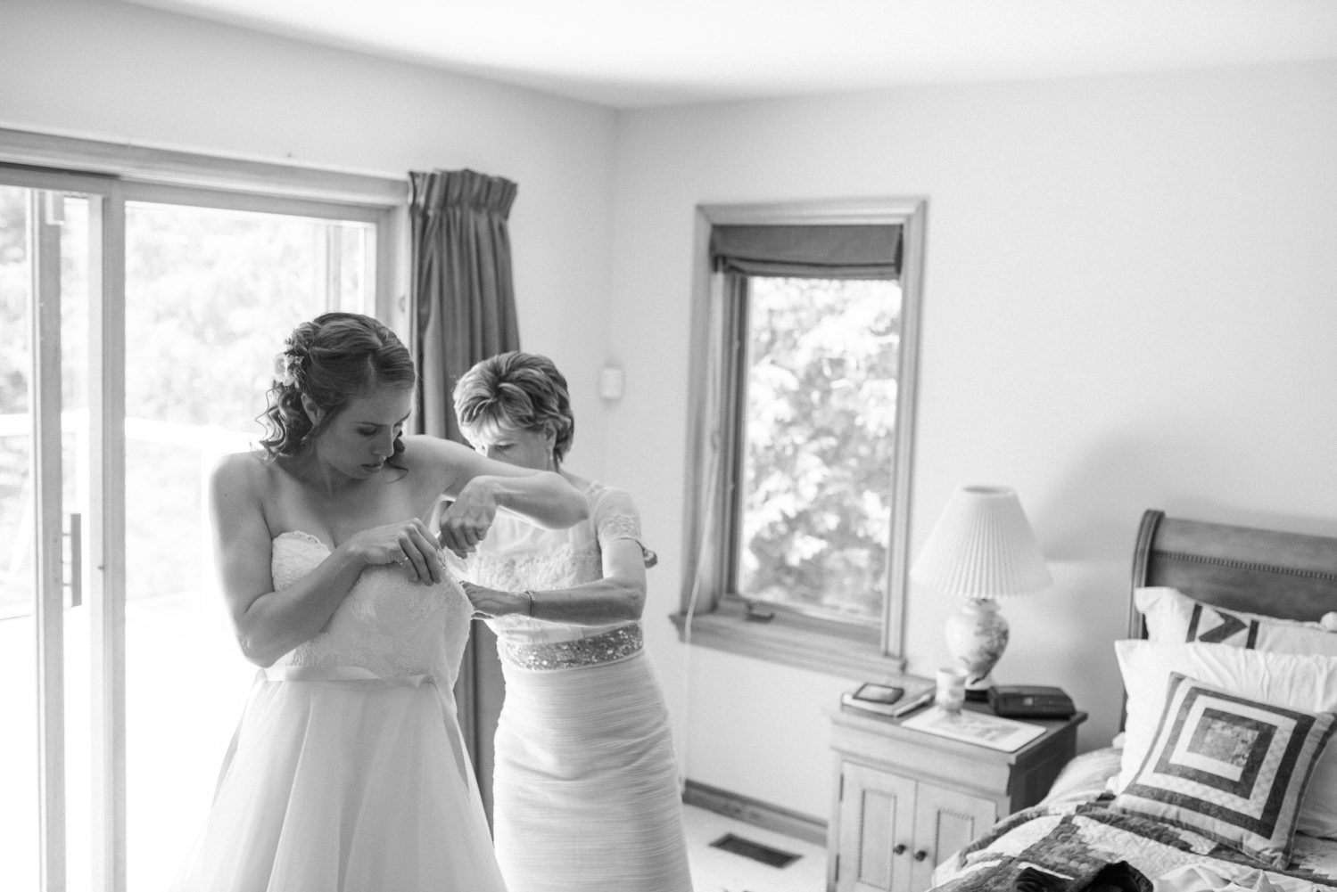 Mom helping her daughter with wedding dress