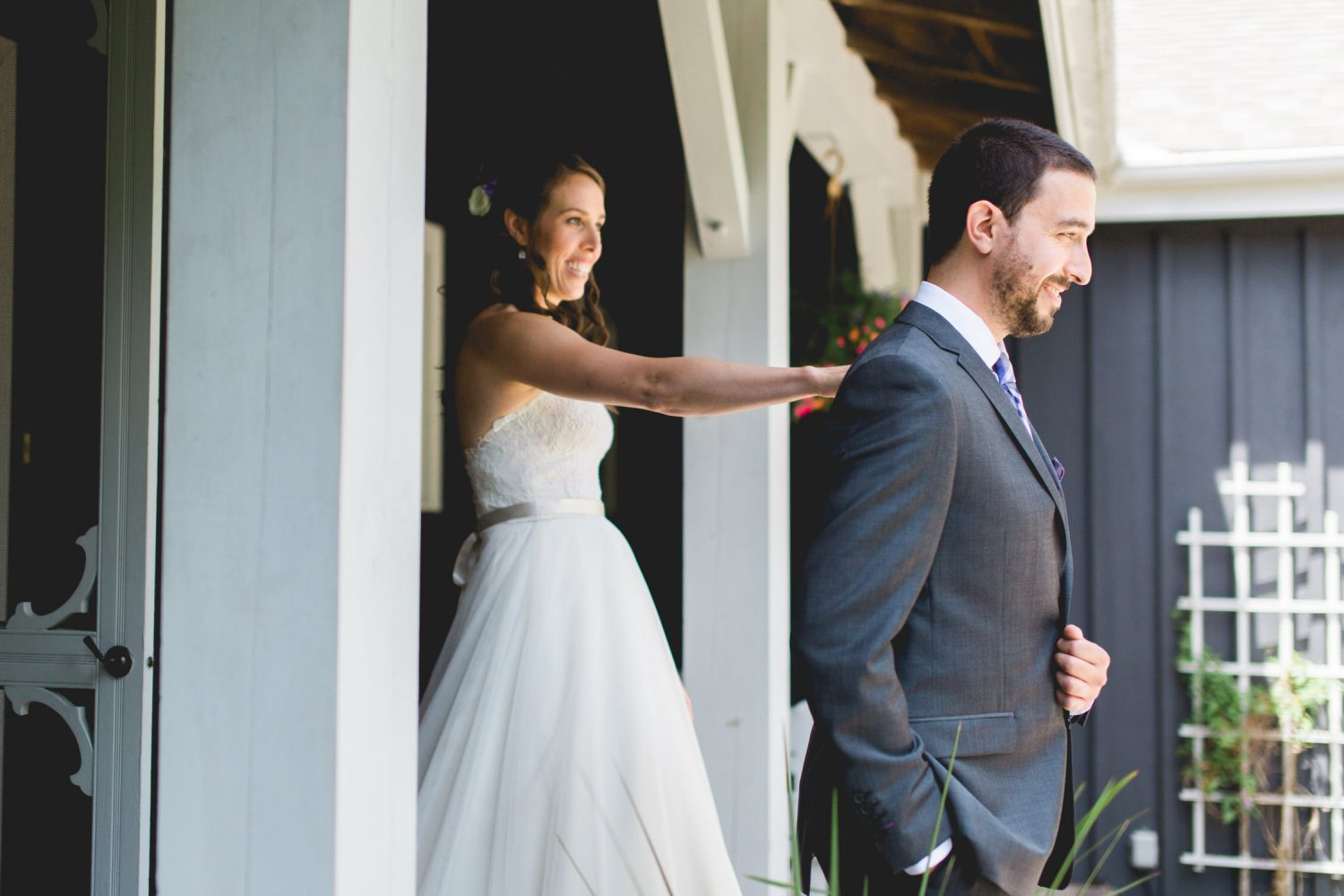 Bride taps groom's shoulder during the first look