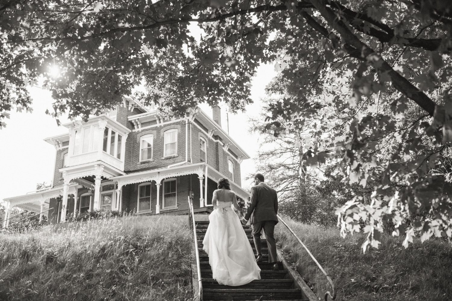 Bride and groom walking up steps towards house