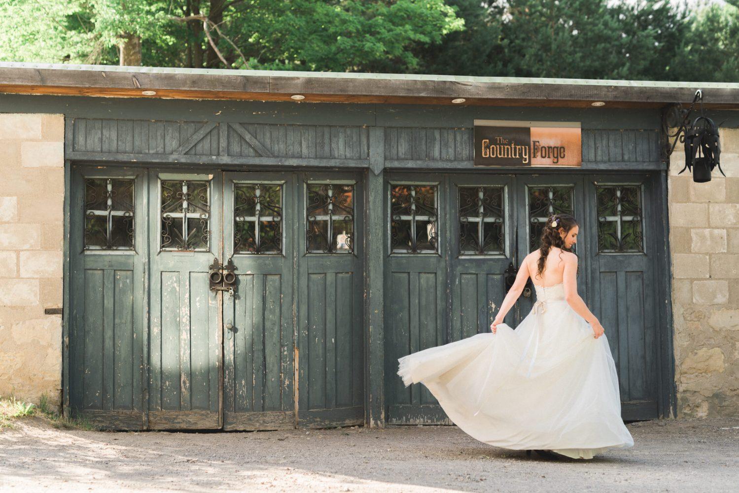 Bride swings her dress in front of garage door at Alton Mill