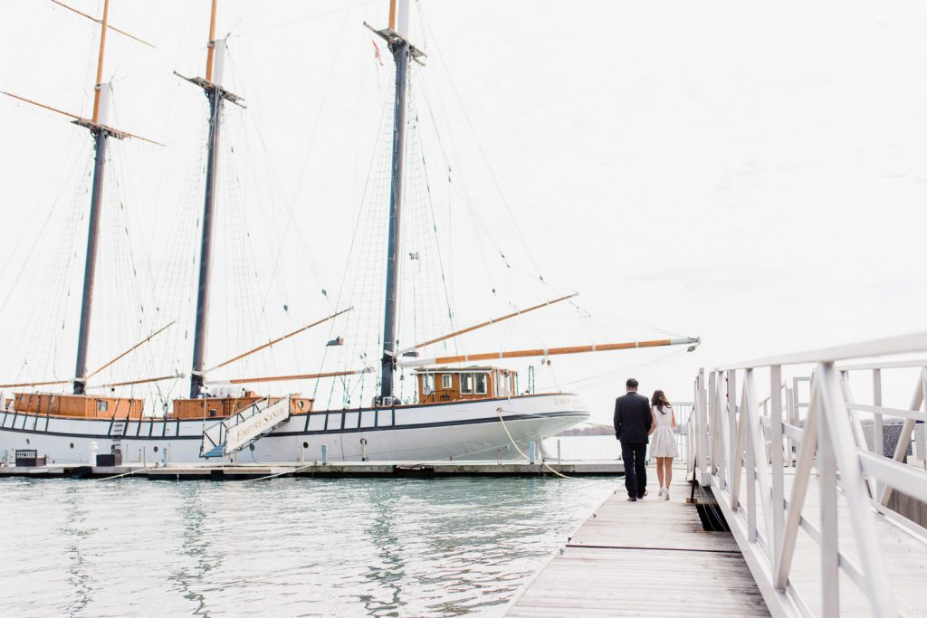 Couple walking towards sailboat at Harbourfront in Toronto