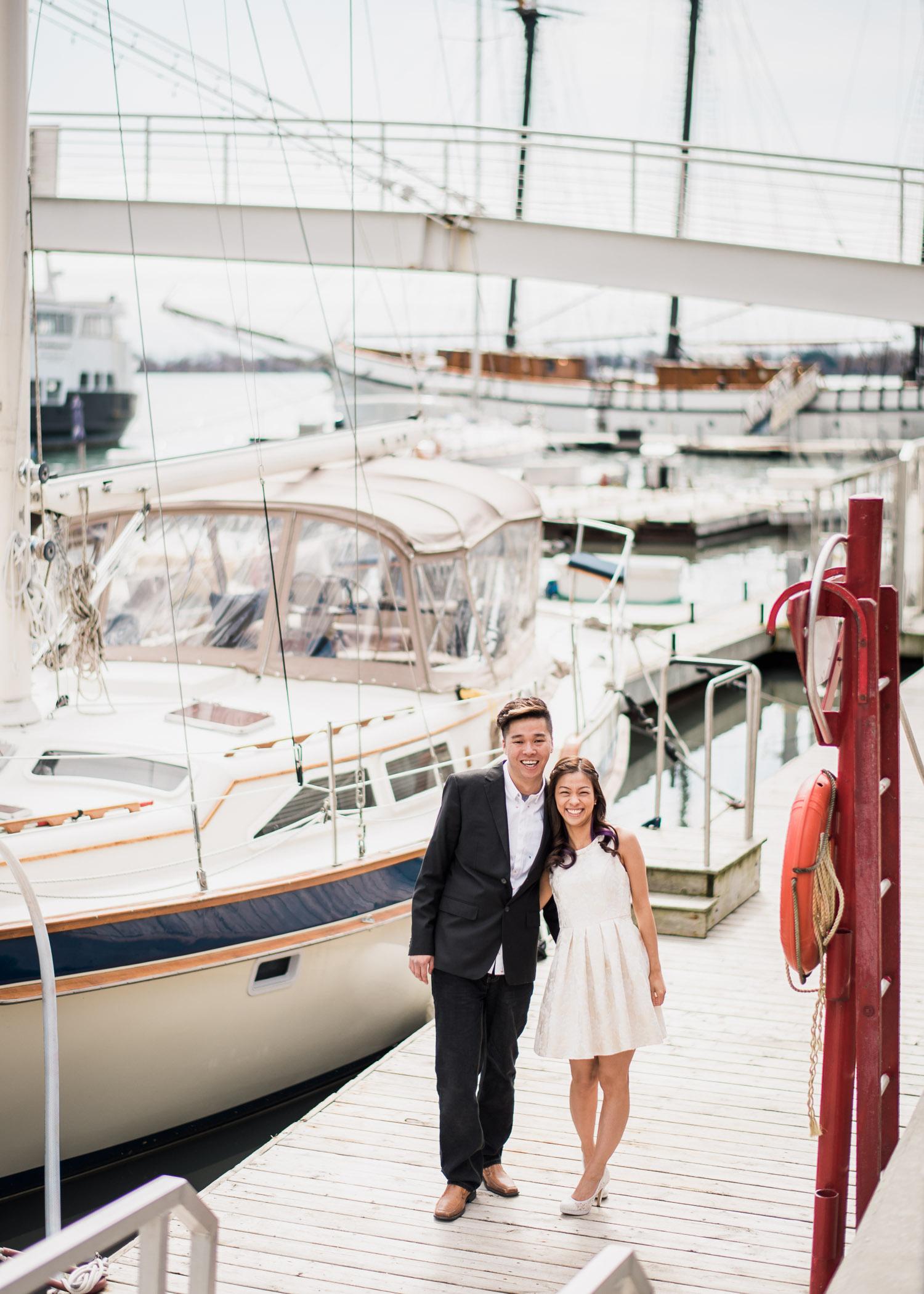 Couple staring at camera, next to a sailboat at Harbourfront Toronto
