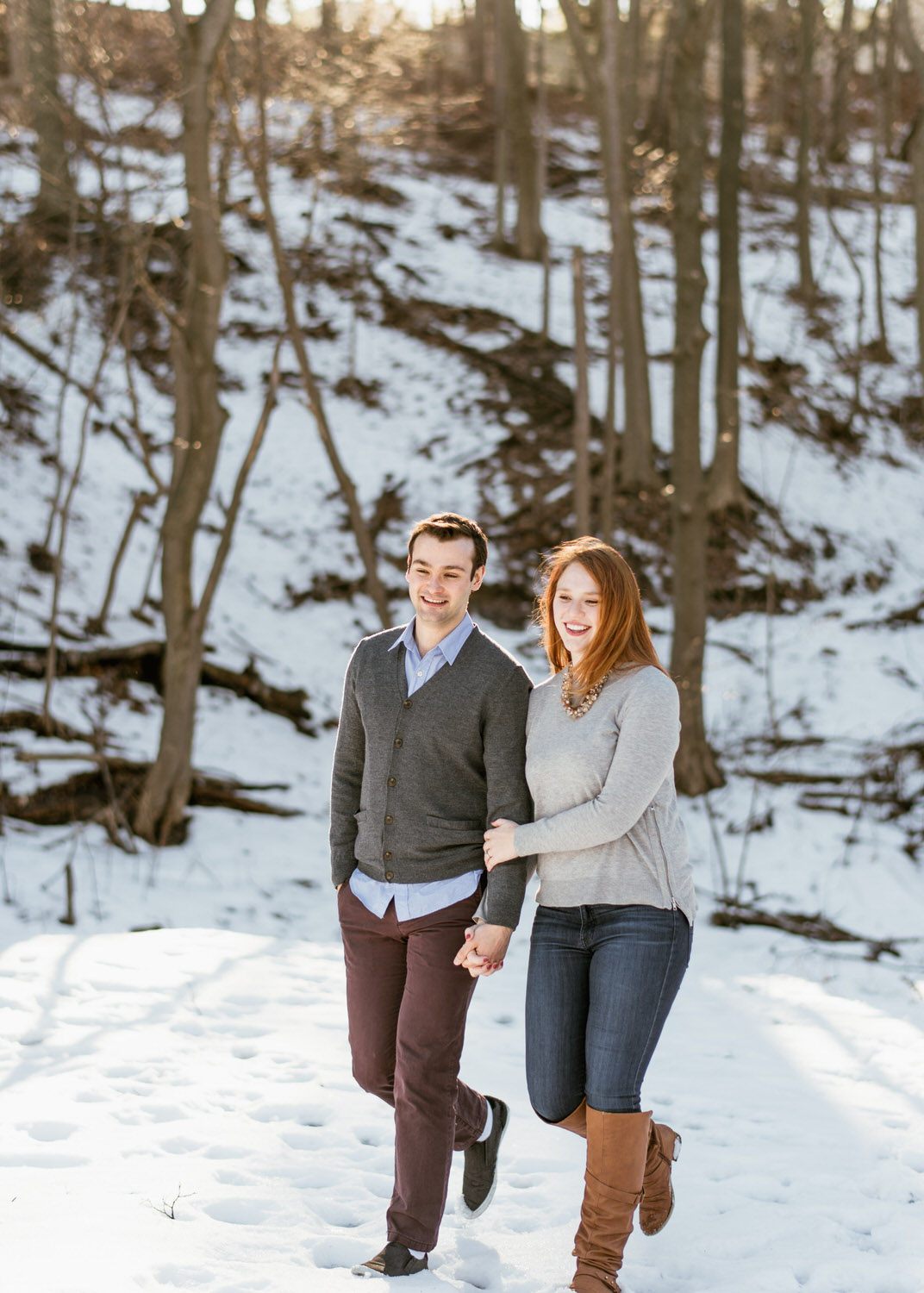 Couple walking through woods during engagement session in Toronto