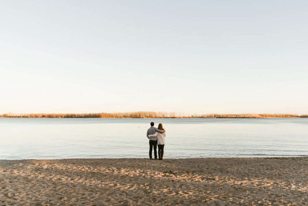 Wide shot of couple on the beach looking at the island in the horizon at Cherry Beach