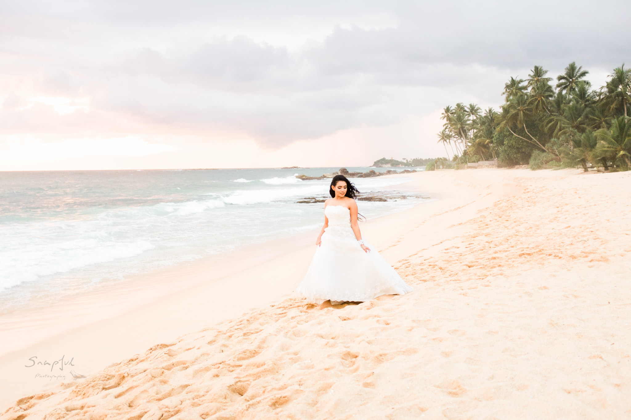 Bride walking on the beach in Sri lanka with palm trees in the background