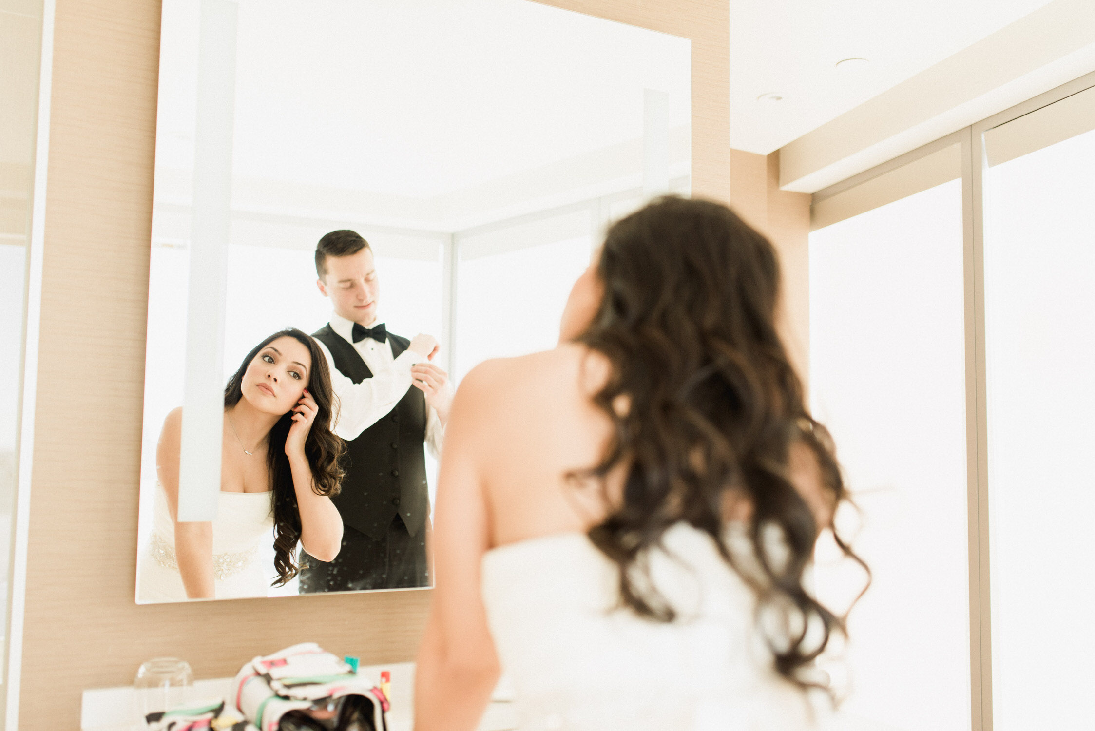 Bride putting on earrings in hotel room at Delta in Toronto