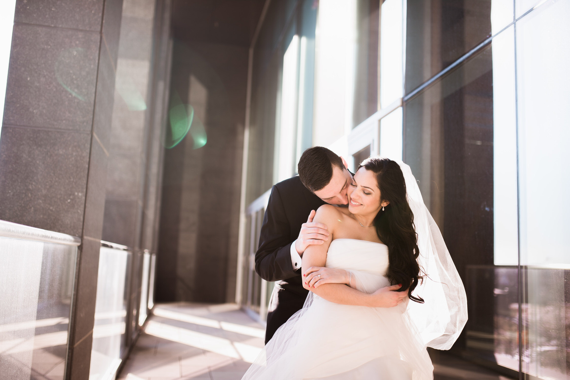 groom kisses bride from behind during elopement at Delta Toronto hotel