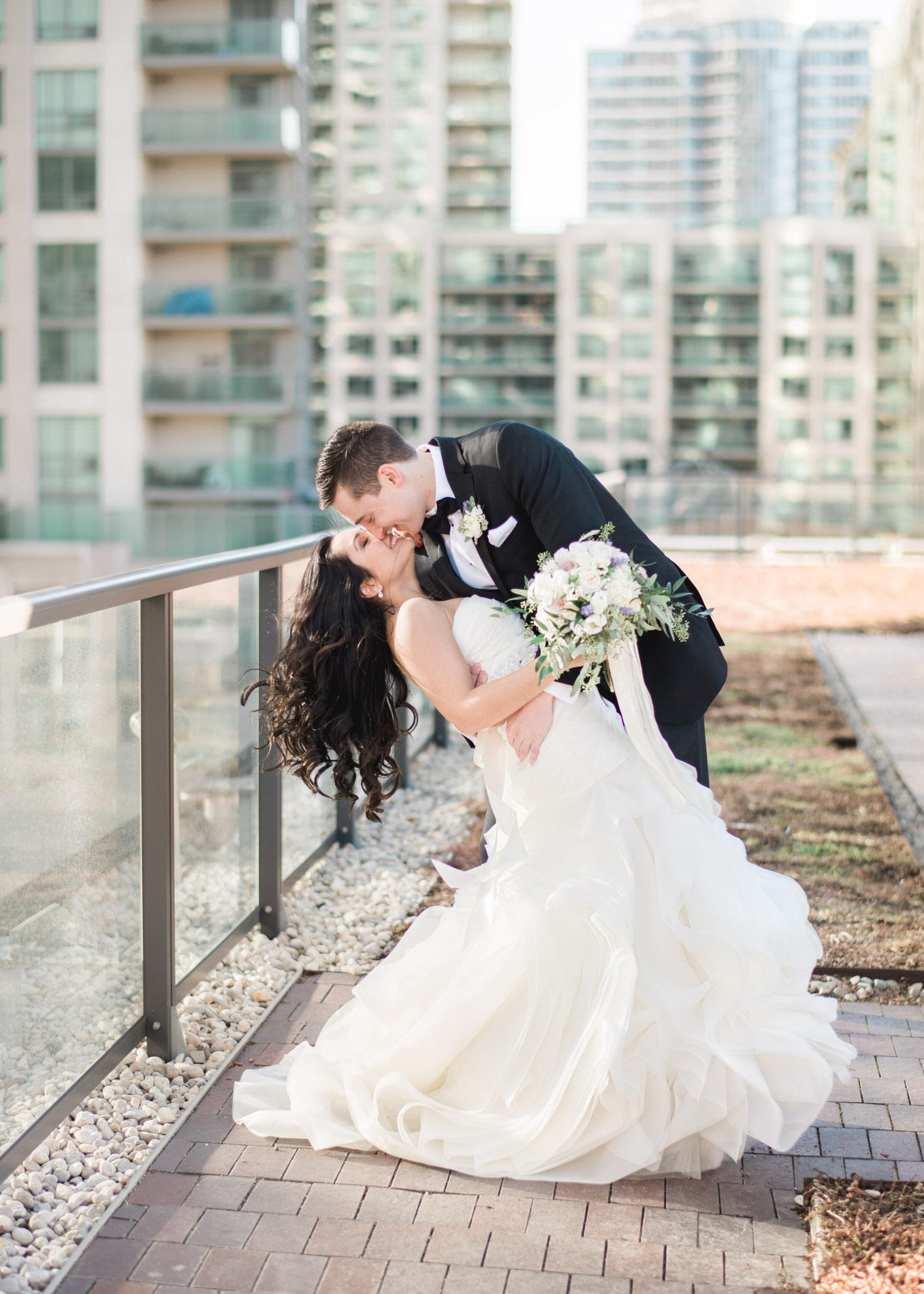 Grooms dips bride for a kiss on rooftop of Delta hotel in Toronto