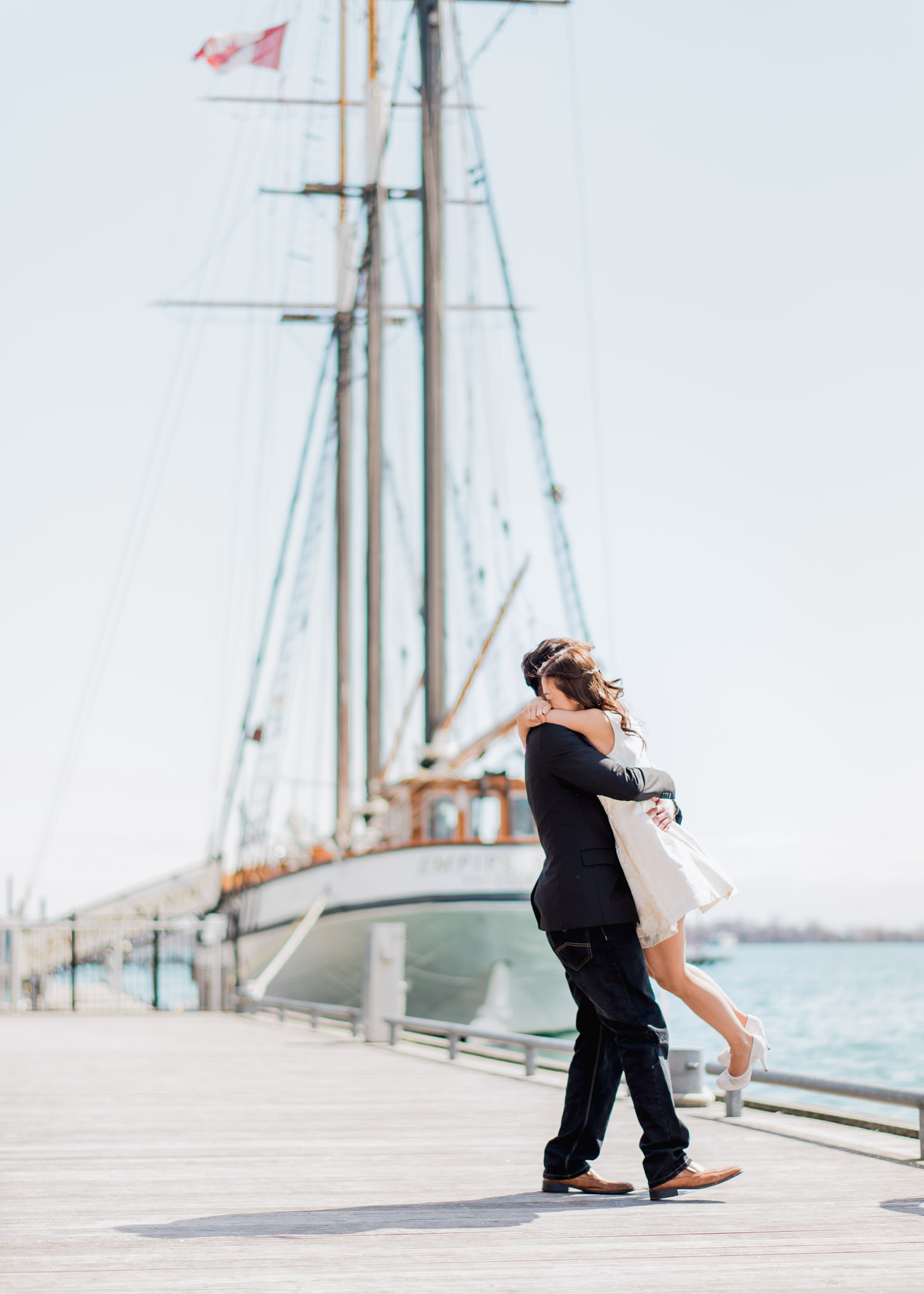 Eric spins Joan in the air during an engagement session at Harbourfront Toronto