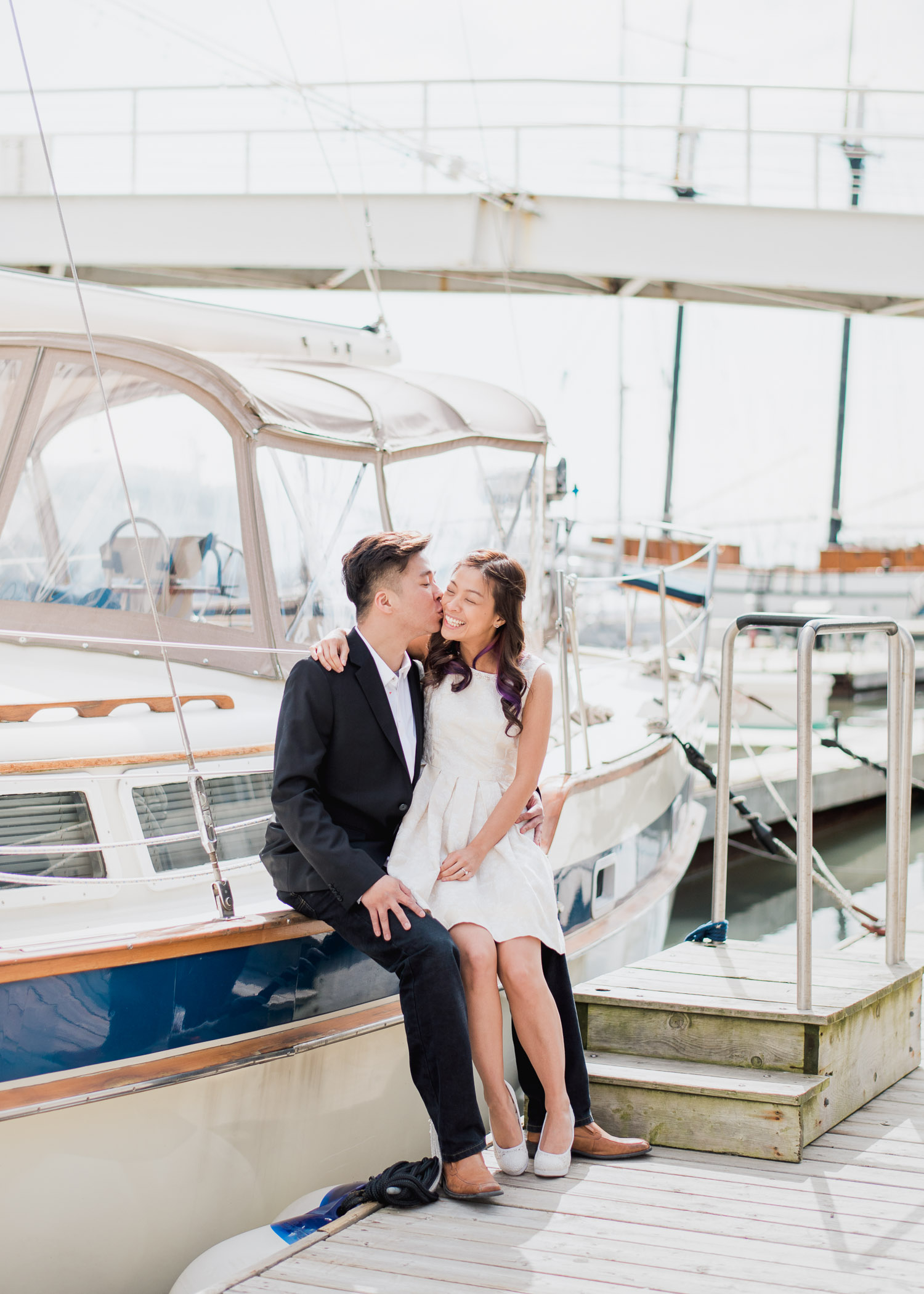 Couple sitting on sailboat sharing a kiss at Harbourfront Toronto