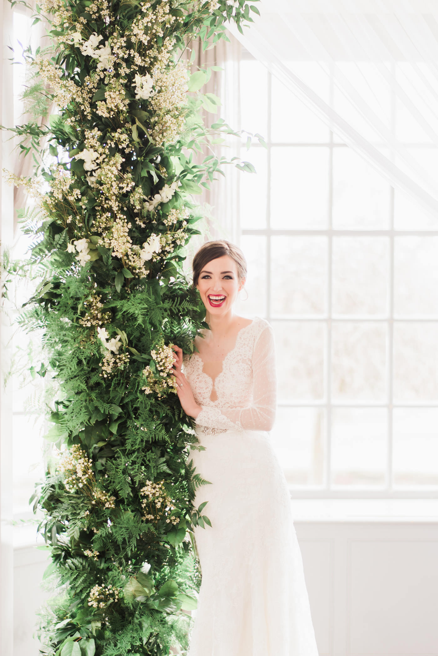 Bride laughing beside ceremony arch at Estates of Sunnybrook
