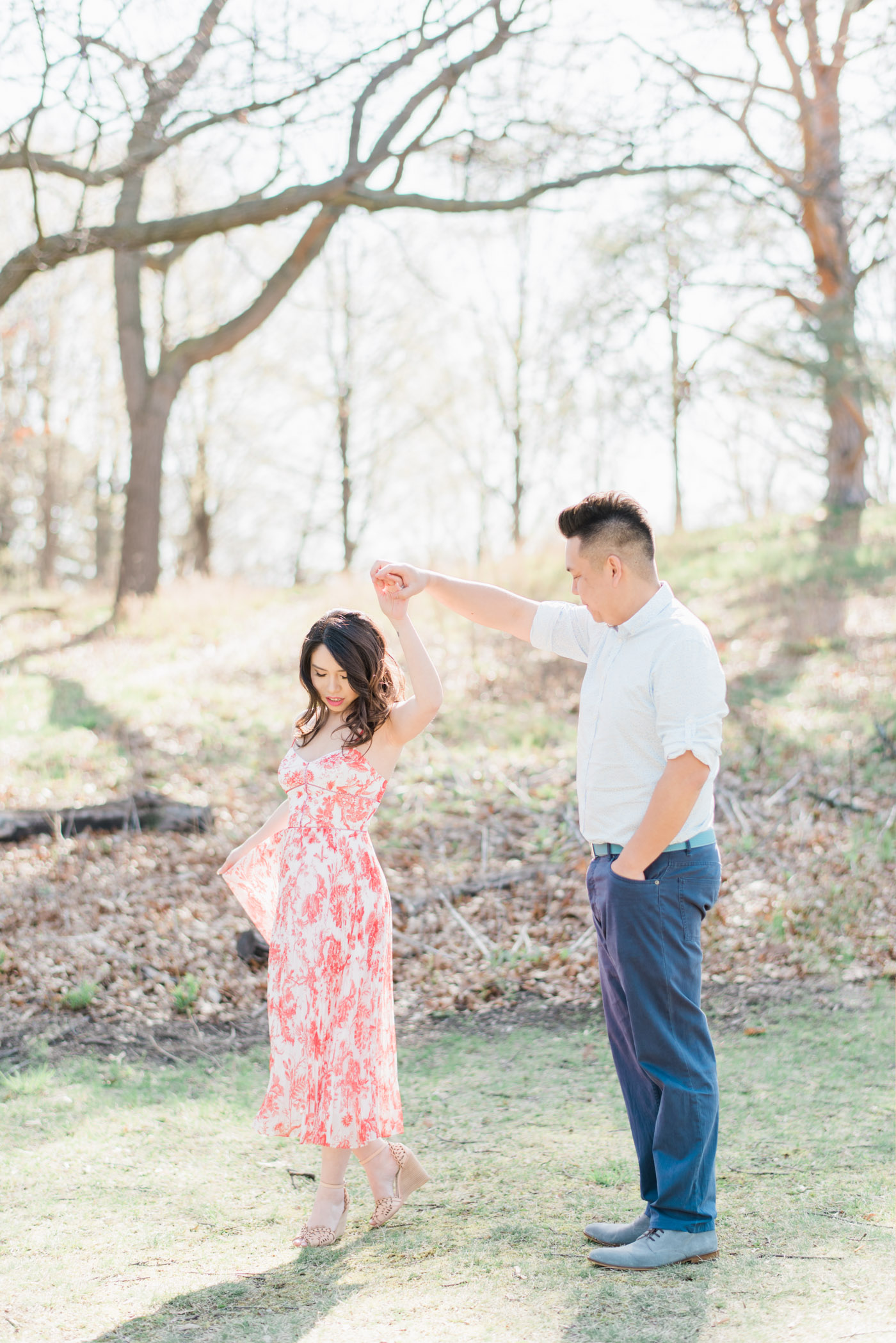 Couple twirling in soft morning light during engagement session at high park in Toronto