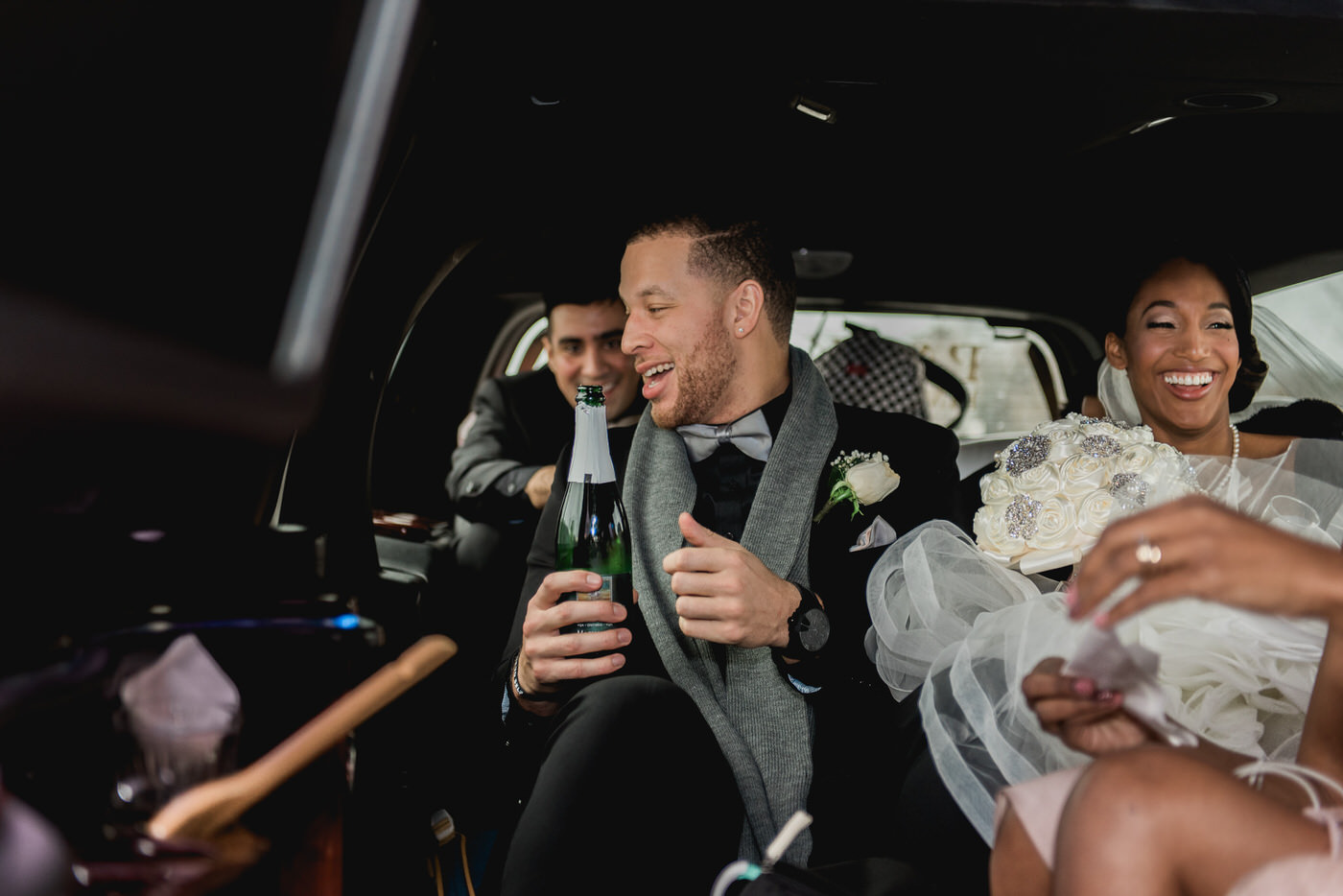 Groom popping a bottle of champagne inside limo in Toronto