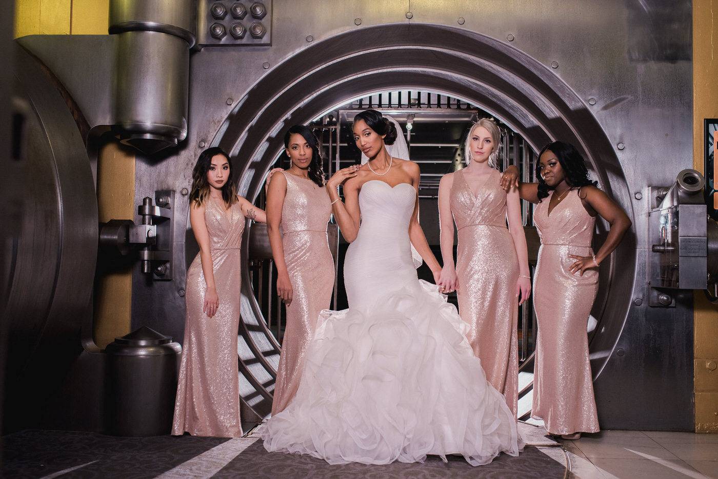 Bride and bridesmaids pose in front of vault inside One King West Hotel Wedding