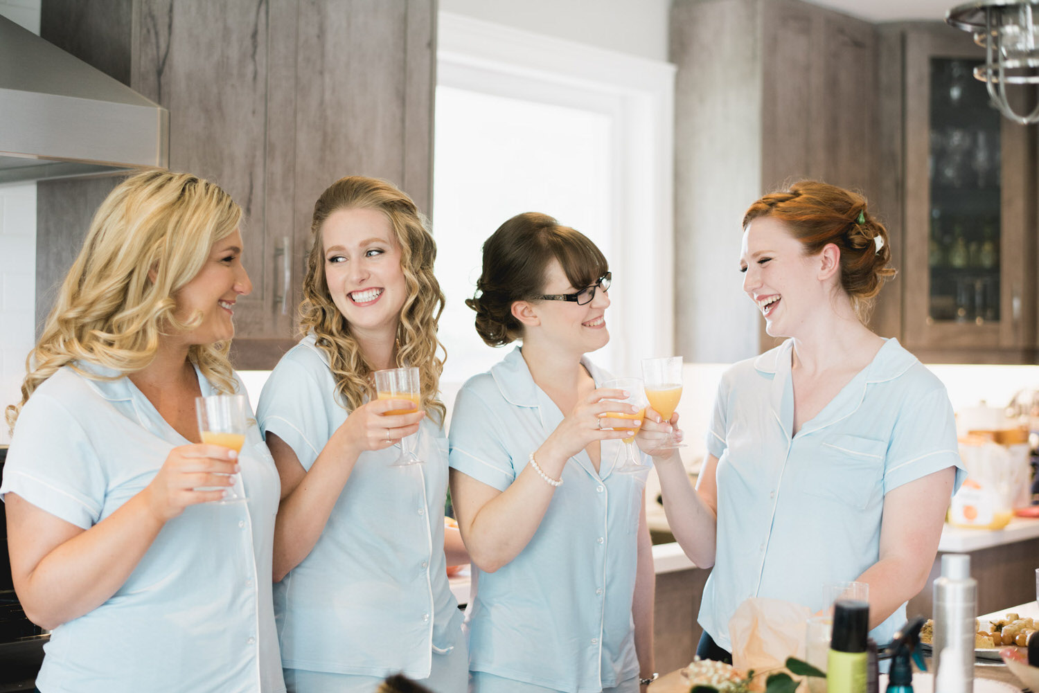 Bride and her girls sharing a glass of champagne in the morning