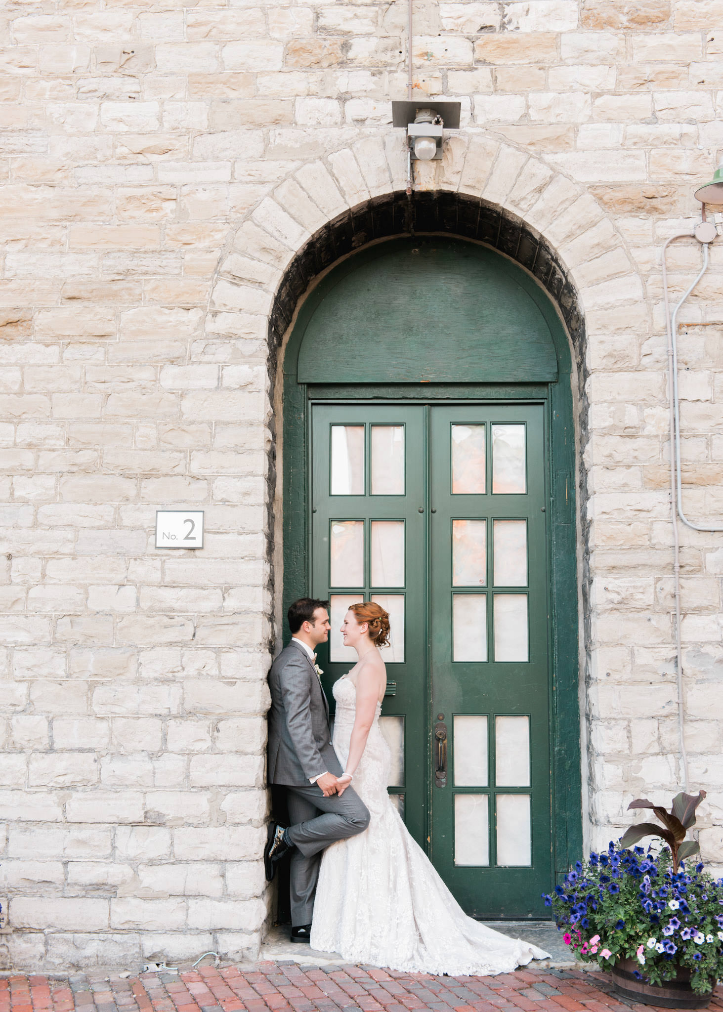 Bride and groom pose at the distillery district in Toronto