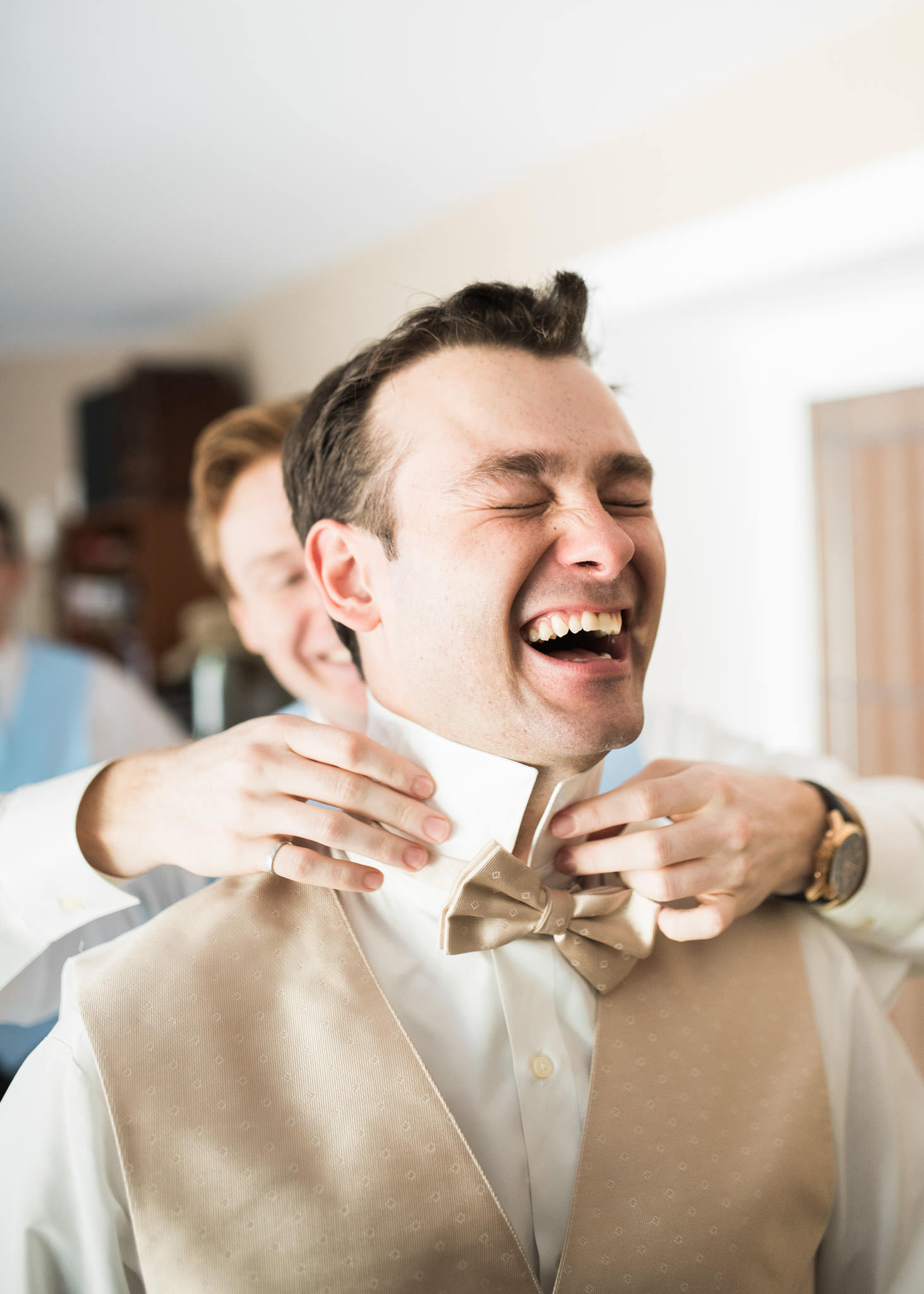 Groom laughing hysterically with his best man