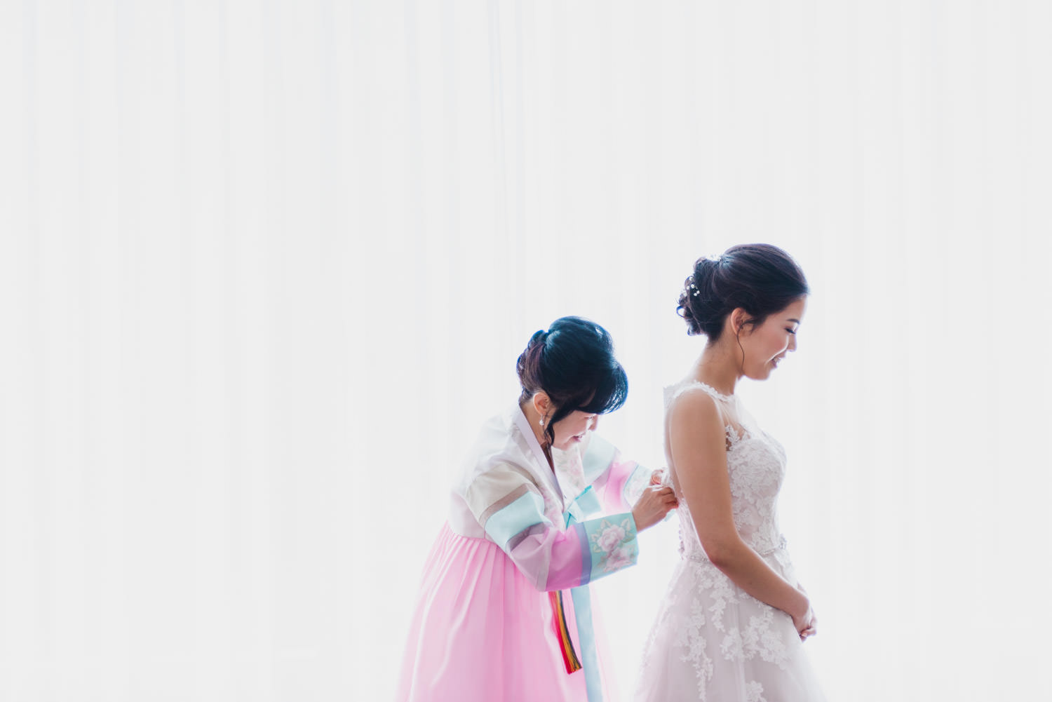 Mom helping bride with her wedding dress at Shangri-La Hotel in Toronto