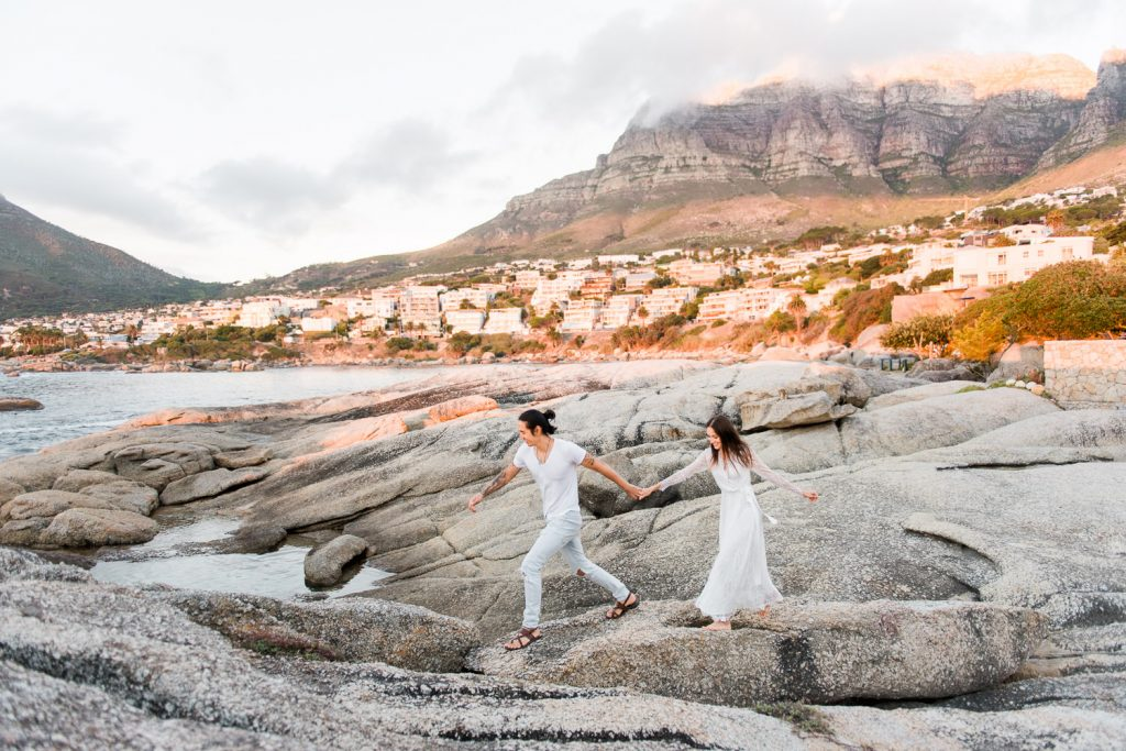 Epic shot of couple hopping on rocks at Camps Bay's engagement session in Cape Town