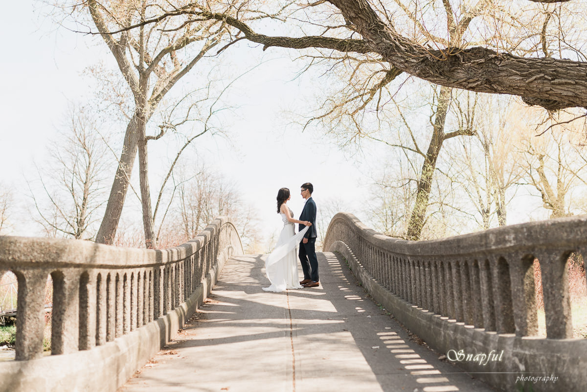 wide angle shot of couple posing on bridge on Centre Island