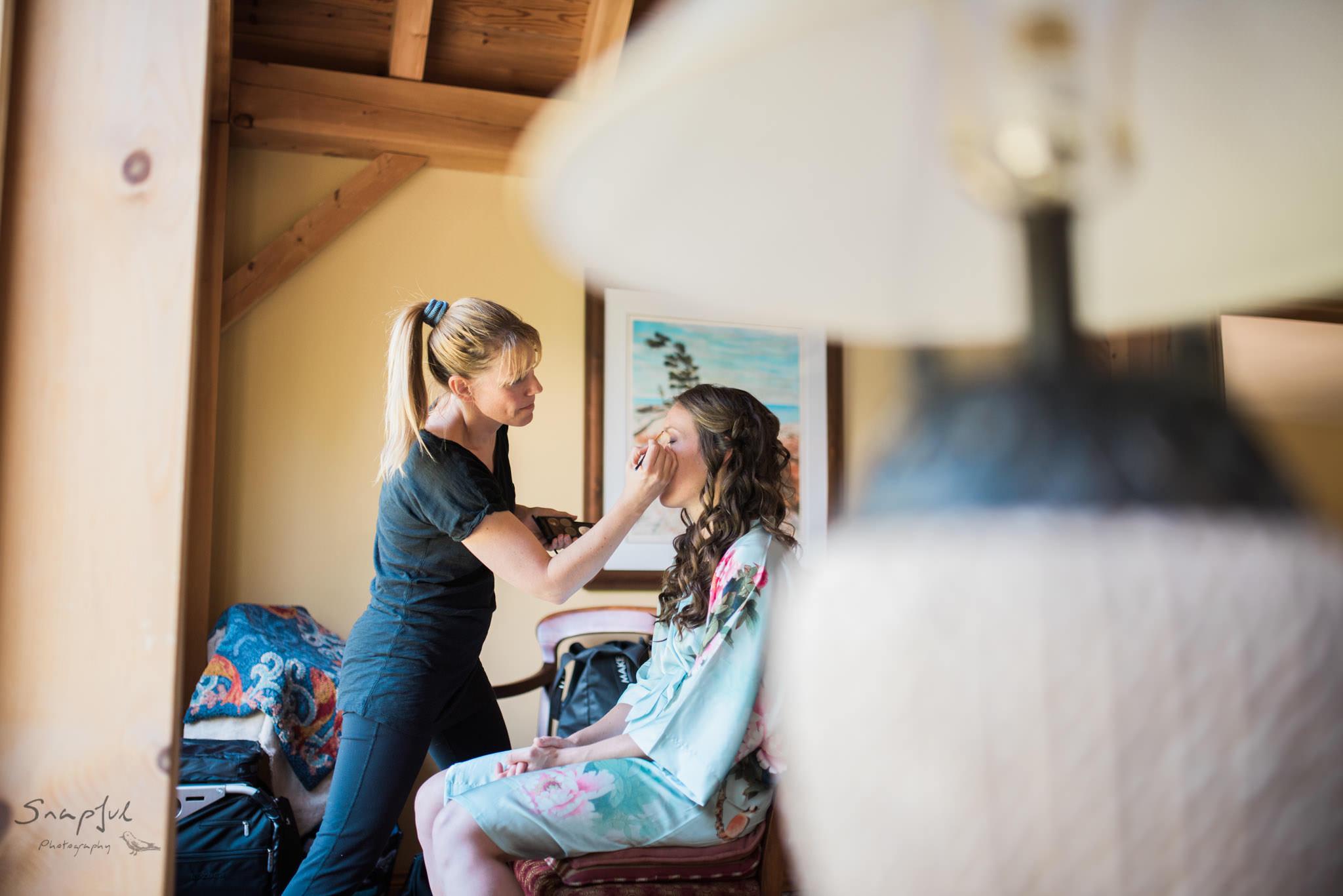 Makeup artist working on bride