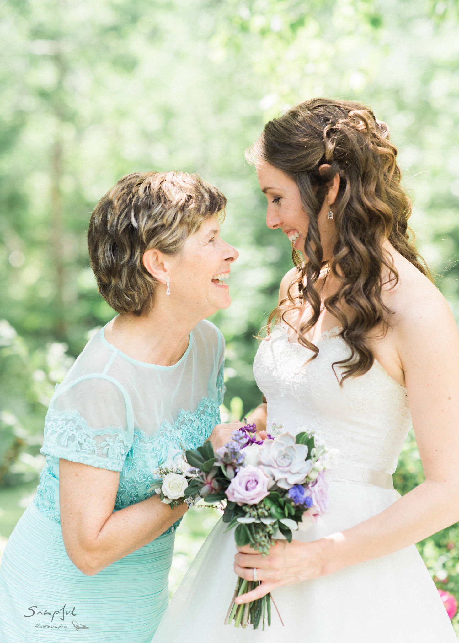 bride and mom share a laugh after the ceremony
