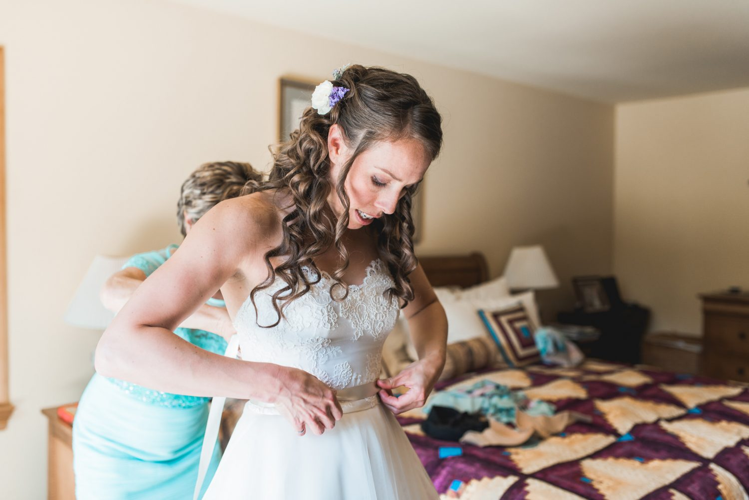 Mom helping bride with her dress
