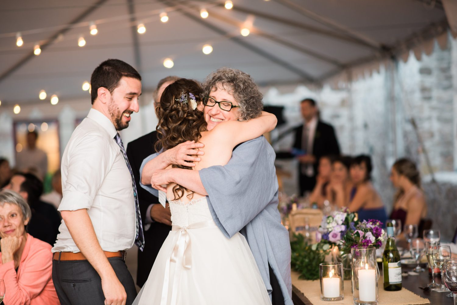 Mother of groom hugs bride after her speech