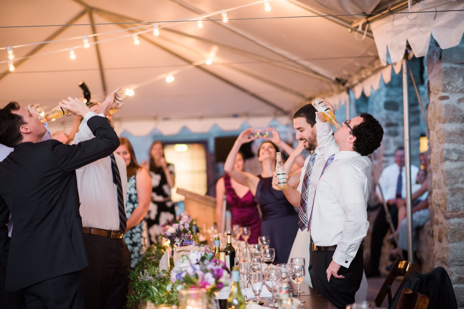 Wedding party chug beers with guests at Alton Mill
