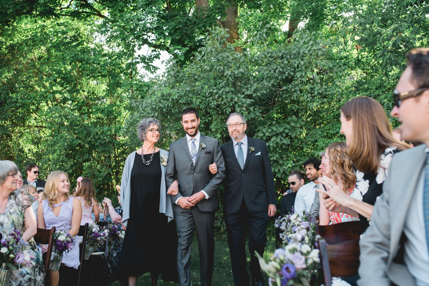 Groom walks down the aisle with his parents