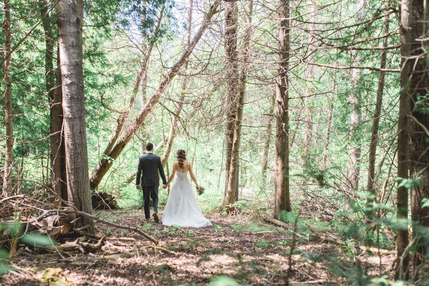 Bride and groom walk into the woods