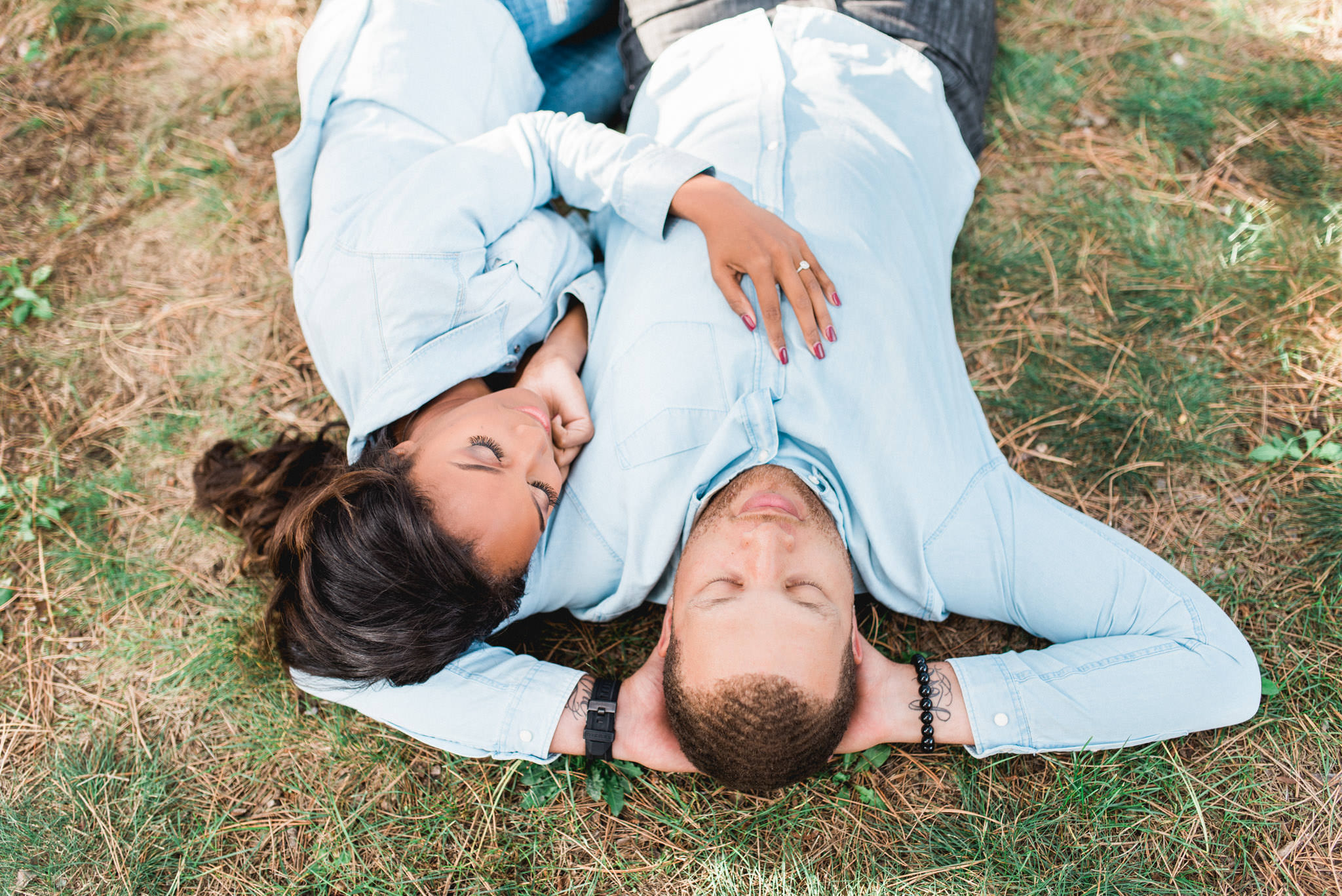 Couple lying on the grass and sharing a laughter at High Park Toronto