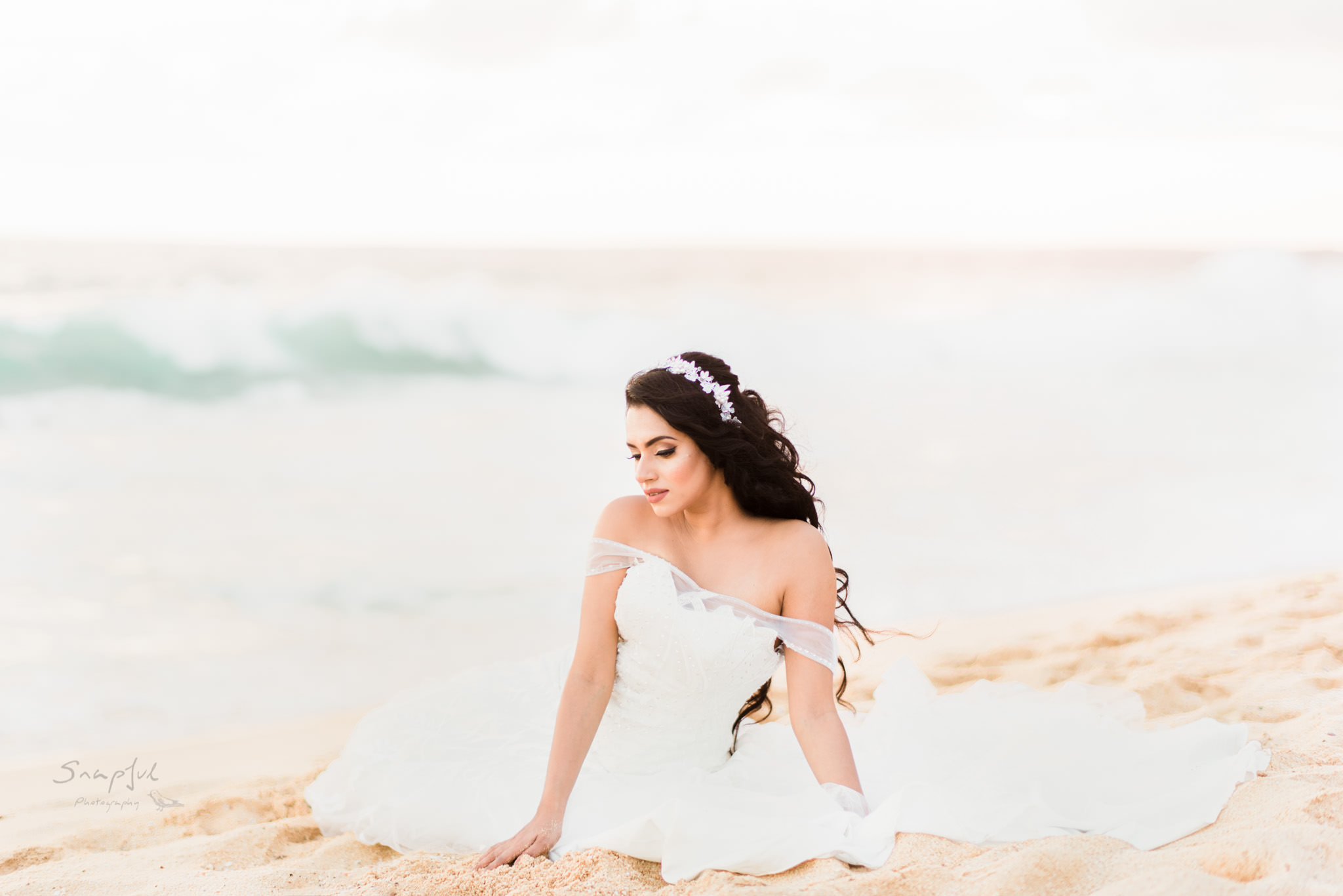 Bride sitting on the sand with waves crashing in Sri Lanka