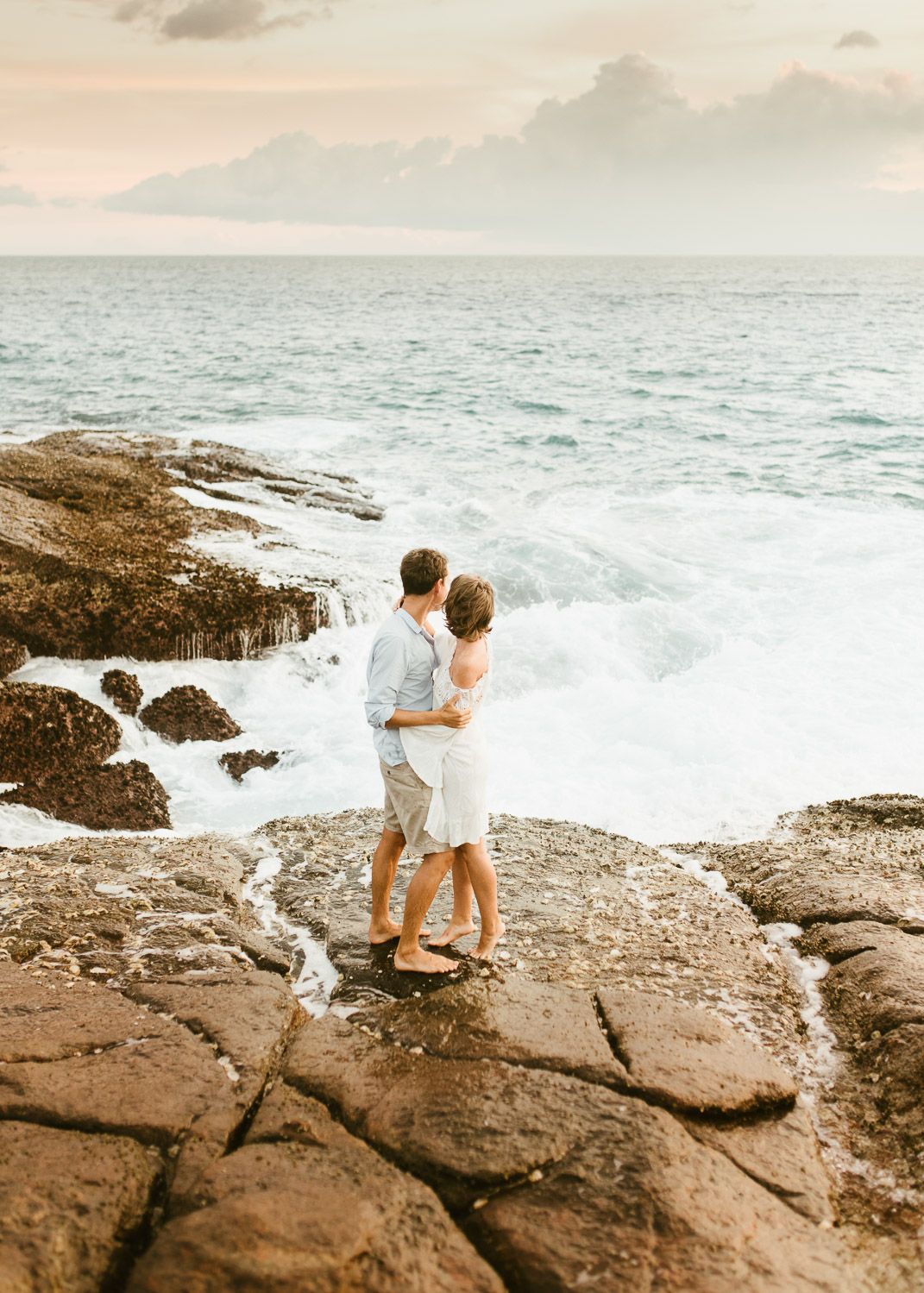 Couple watching waves crash onto rocks in Sri Lanka