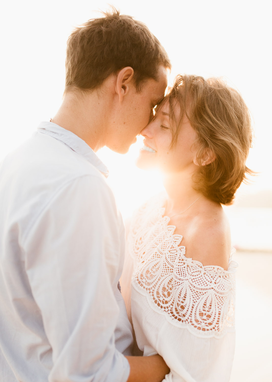 Couple about to kiss and backlit by sun during engagement session in Sri Lanka