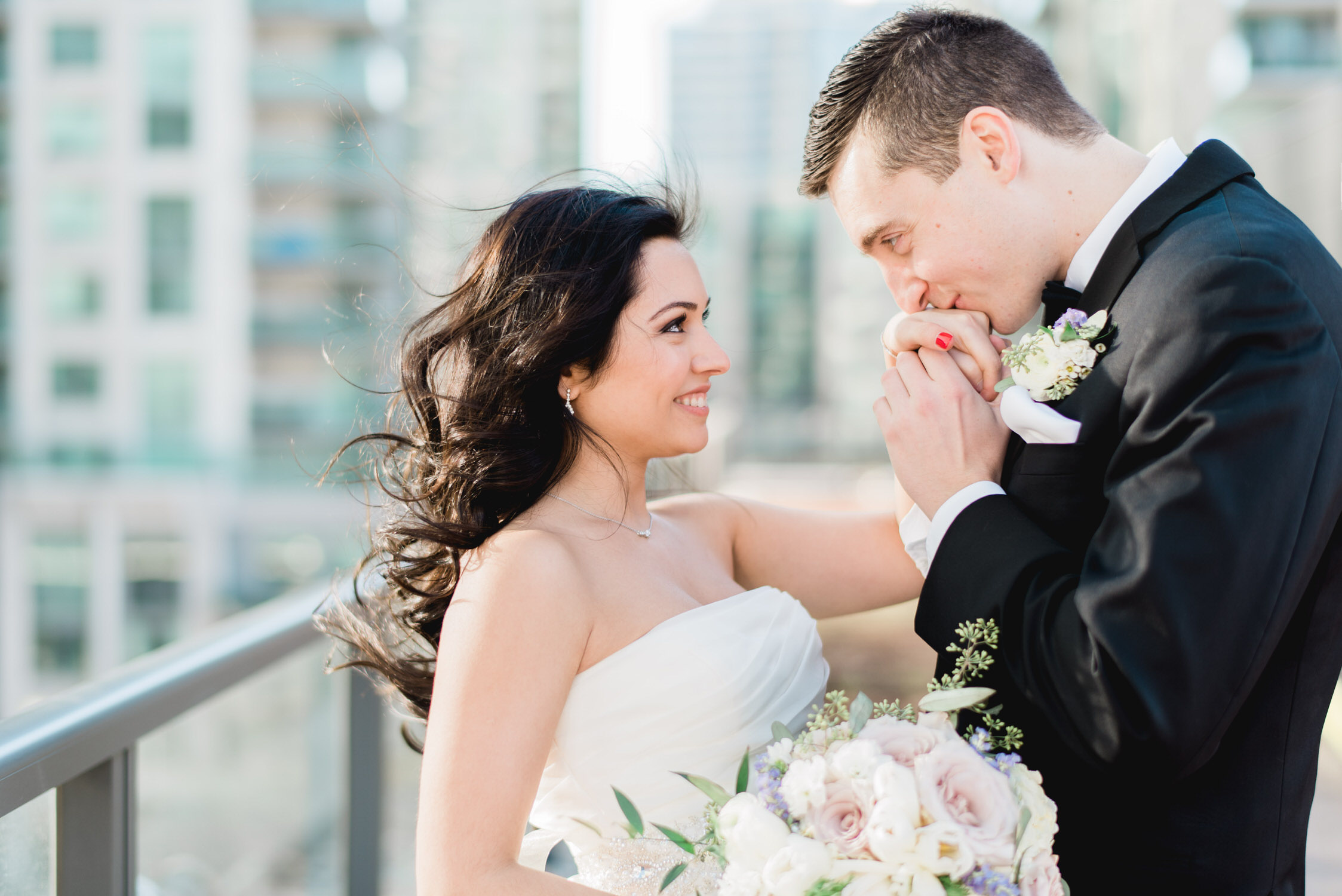 Groom kisses bride's hand on rooftop at Delta hotel in Toronto