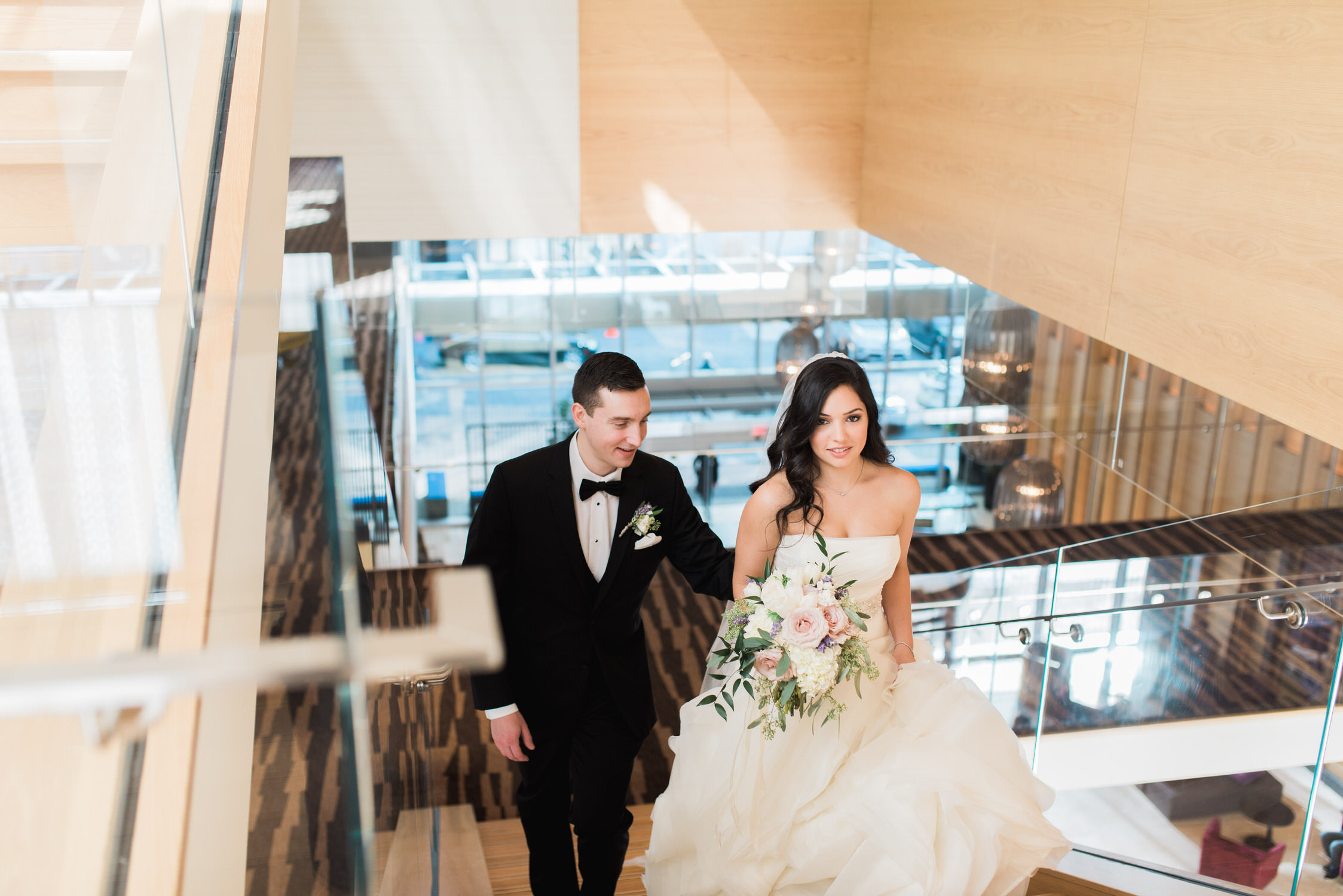Bride and groom walk upstairs at Delta hotel during elopement in Toronto