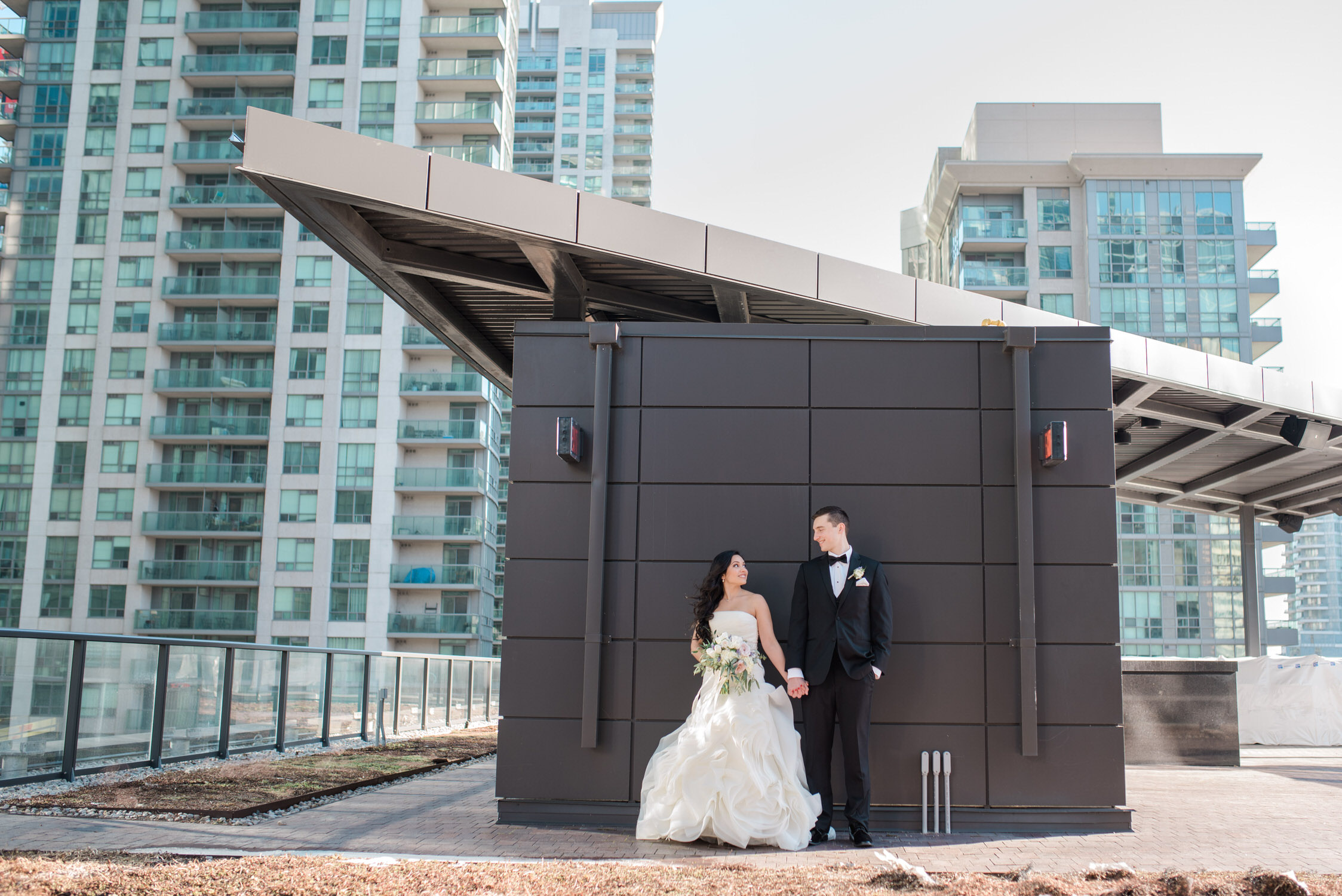 Bride and groom pose on rooftop of delta hotel in toronto