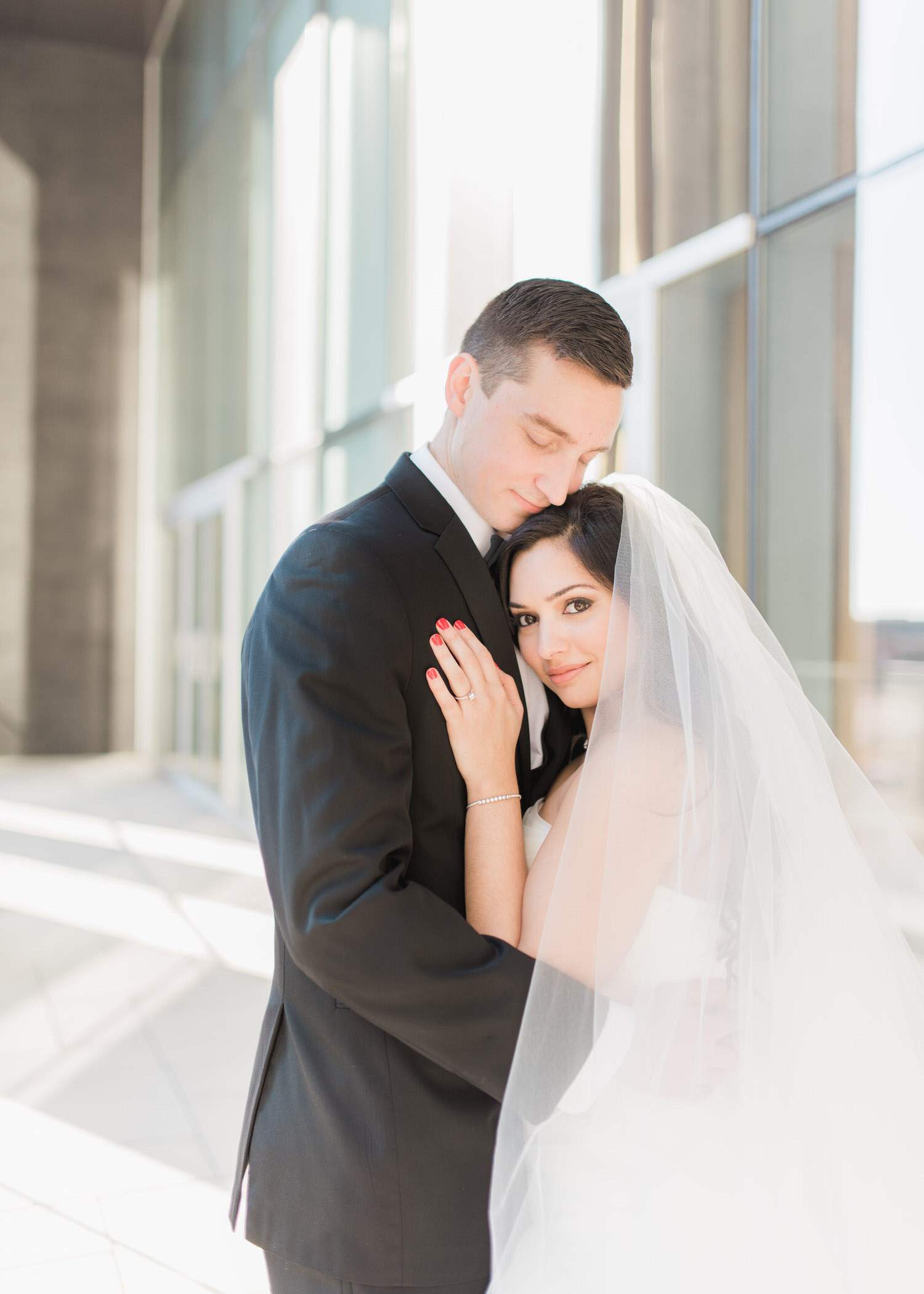 Bride stares at camera while groom is holding her at Delta hotel in Toronto