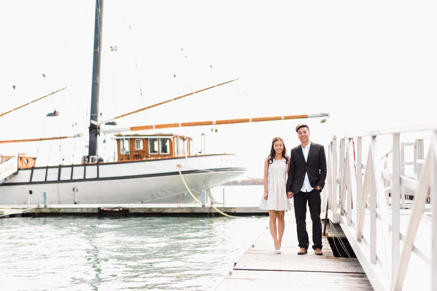 Couple staring at camera besides a sailboat at Harbourfront Toronto