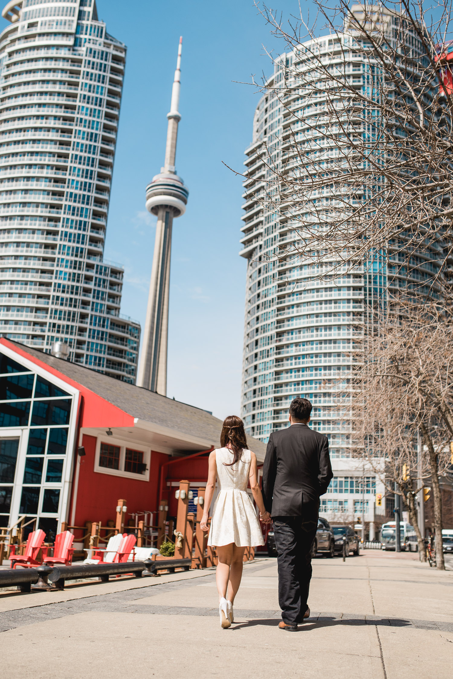 Couple staring at the CN Tower during an engagement session in Toronto