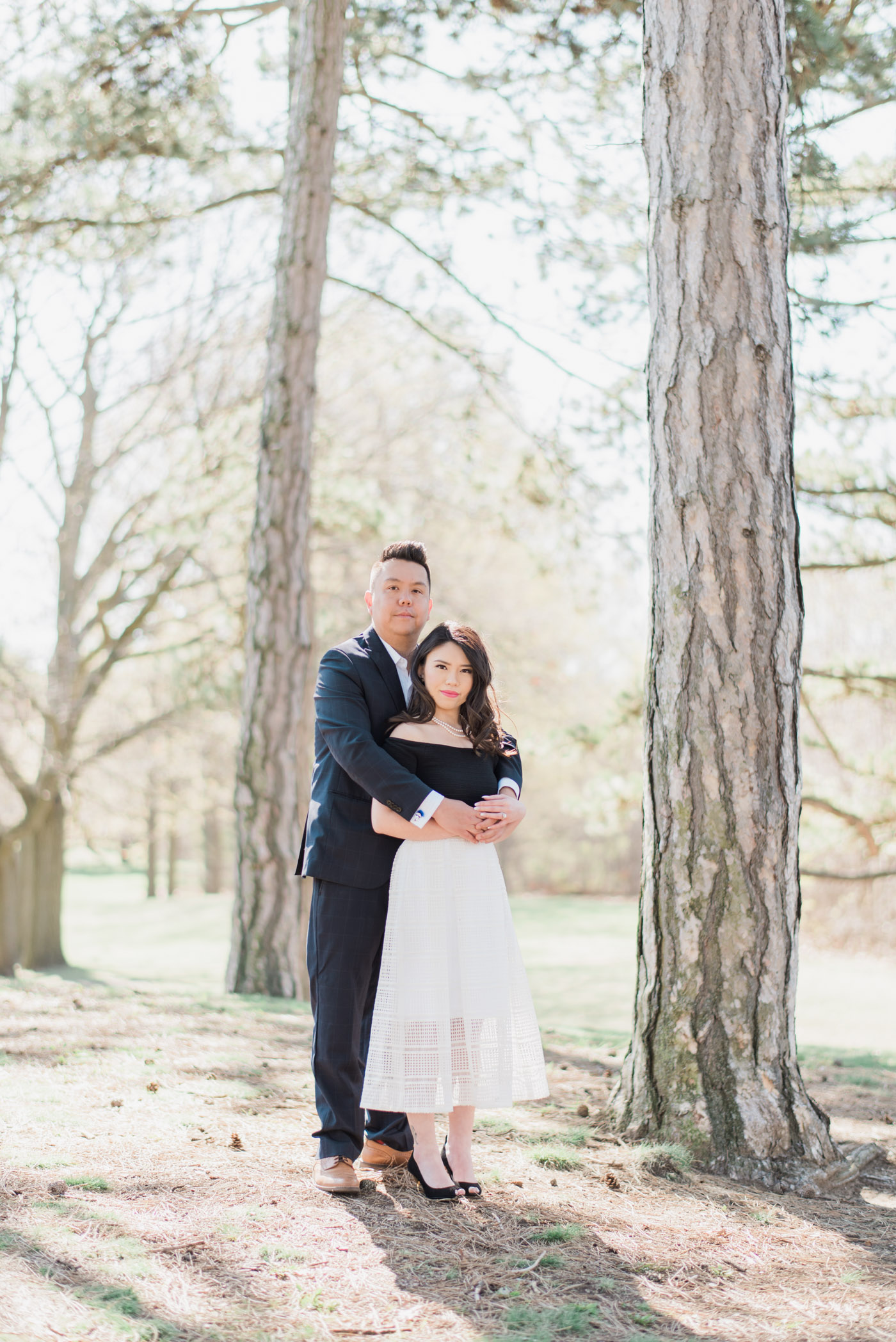 Elegant couple pose during engagement shoot at high park in toronto