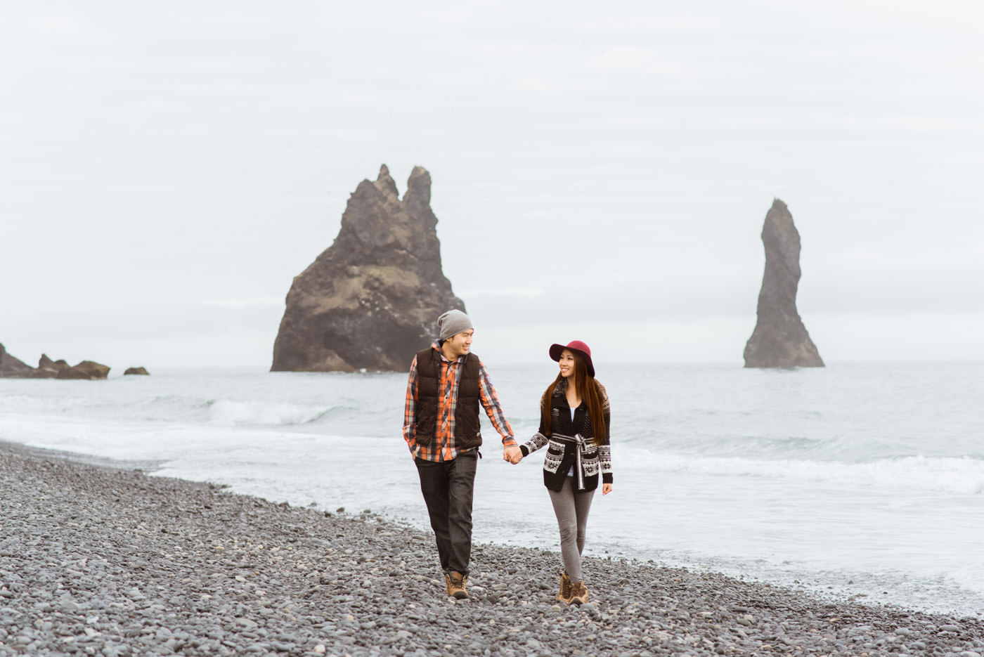 Wedding Photographers walk on black sand beach in Vik Iceland