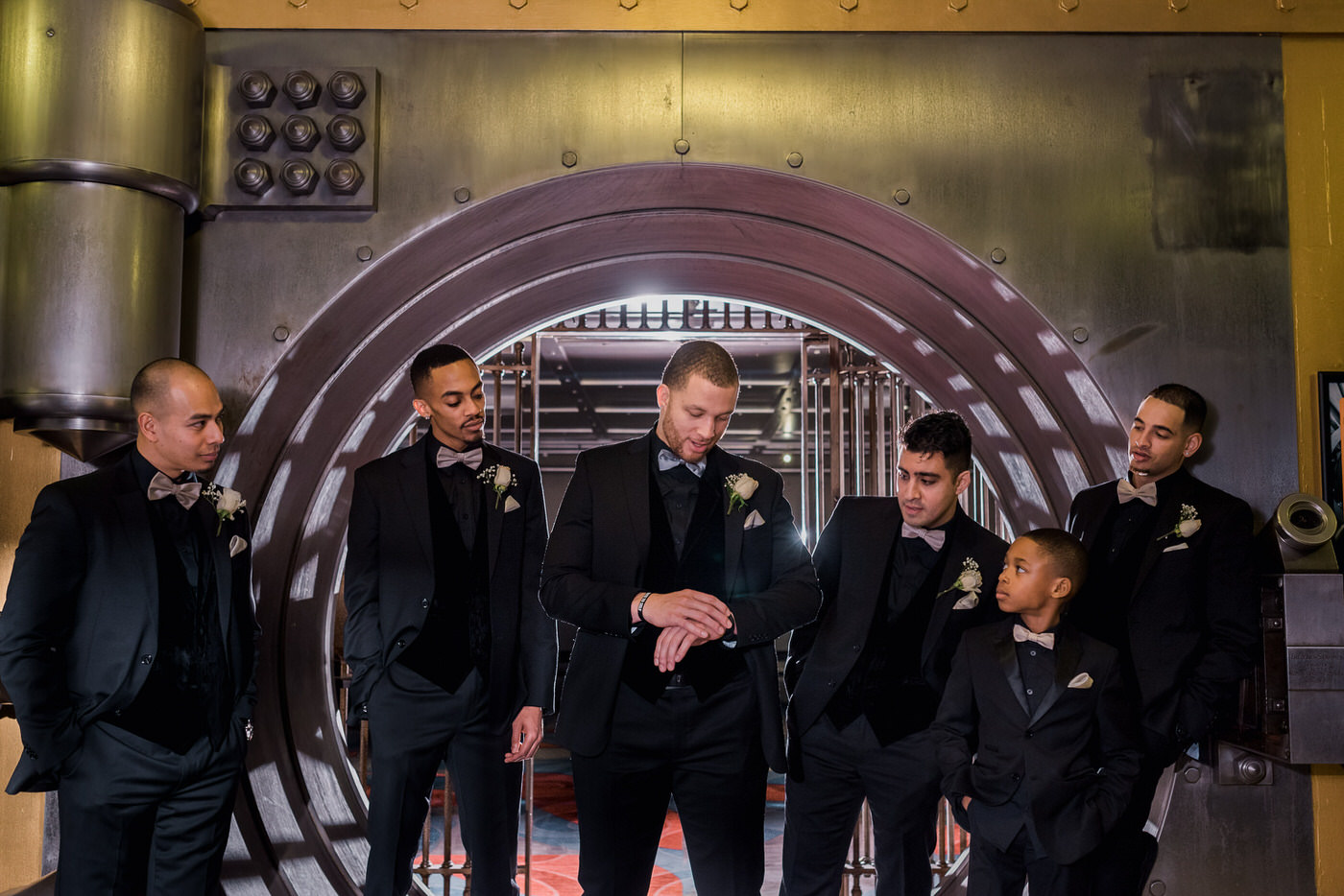 Groom and groosmen posing inside vault at One King West Hotel with off camera flash