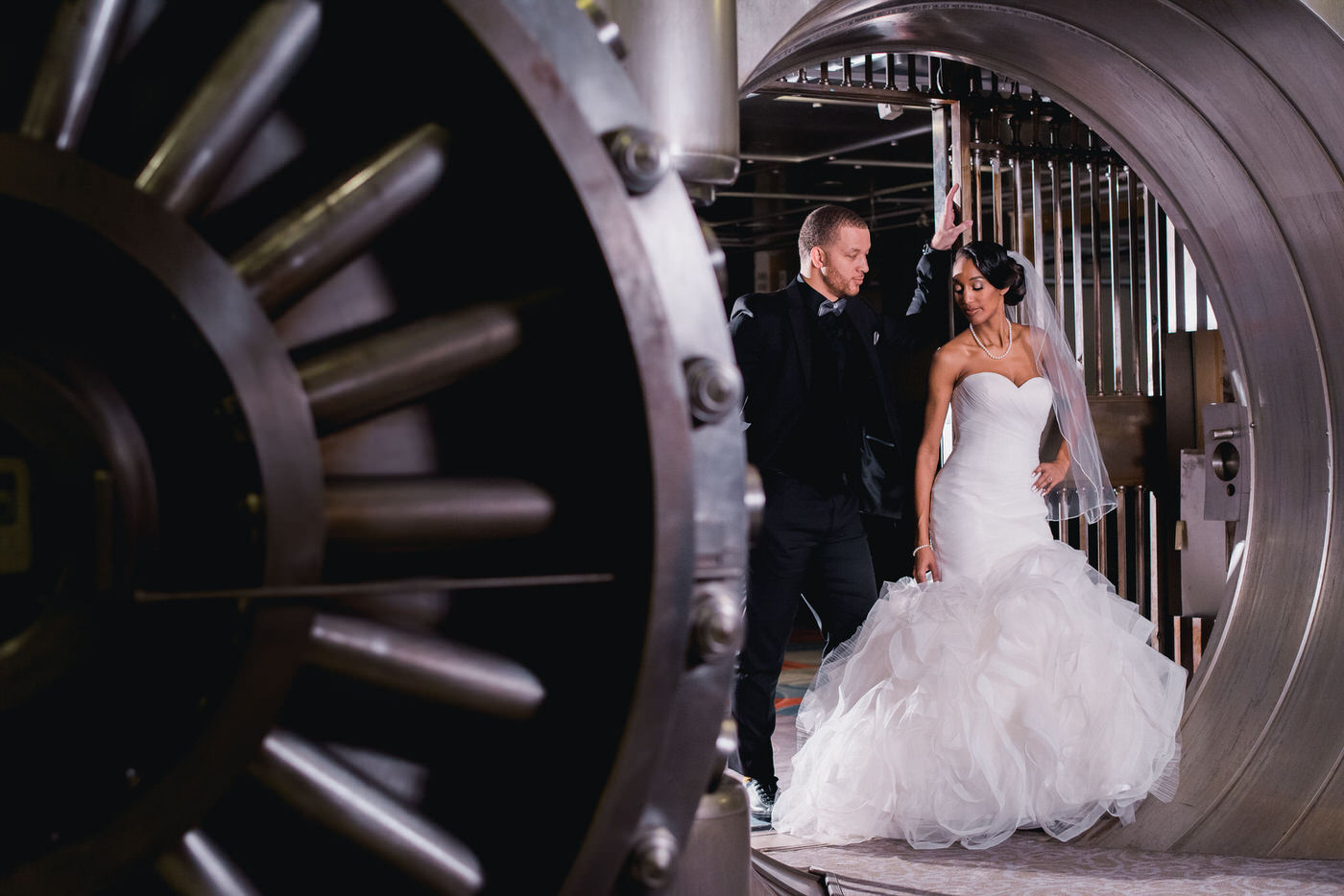 Couple posing inside vault at One King West Hotel with off camera flash