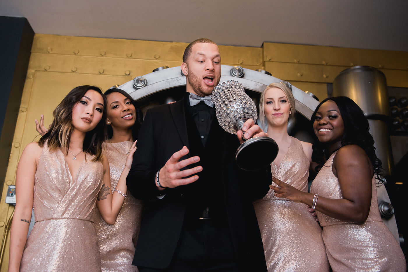 Groom posing with bridesmaids at One King West hotel wedding