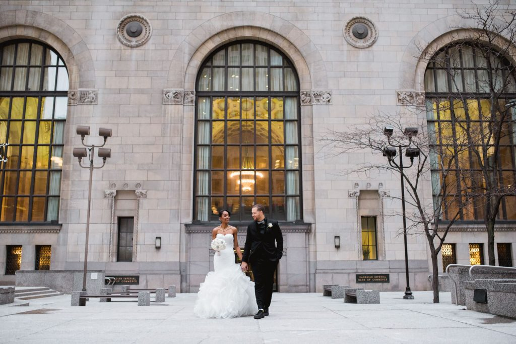 Bride and groom walking downtown at One King Hotel