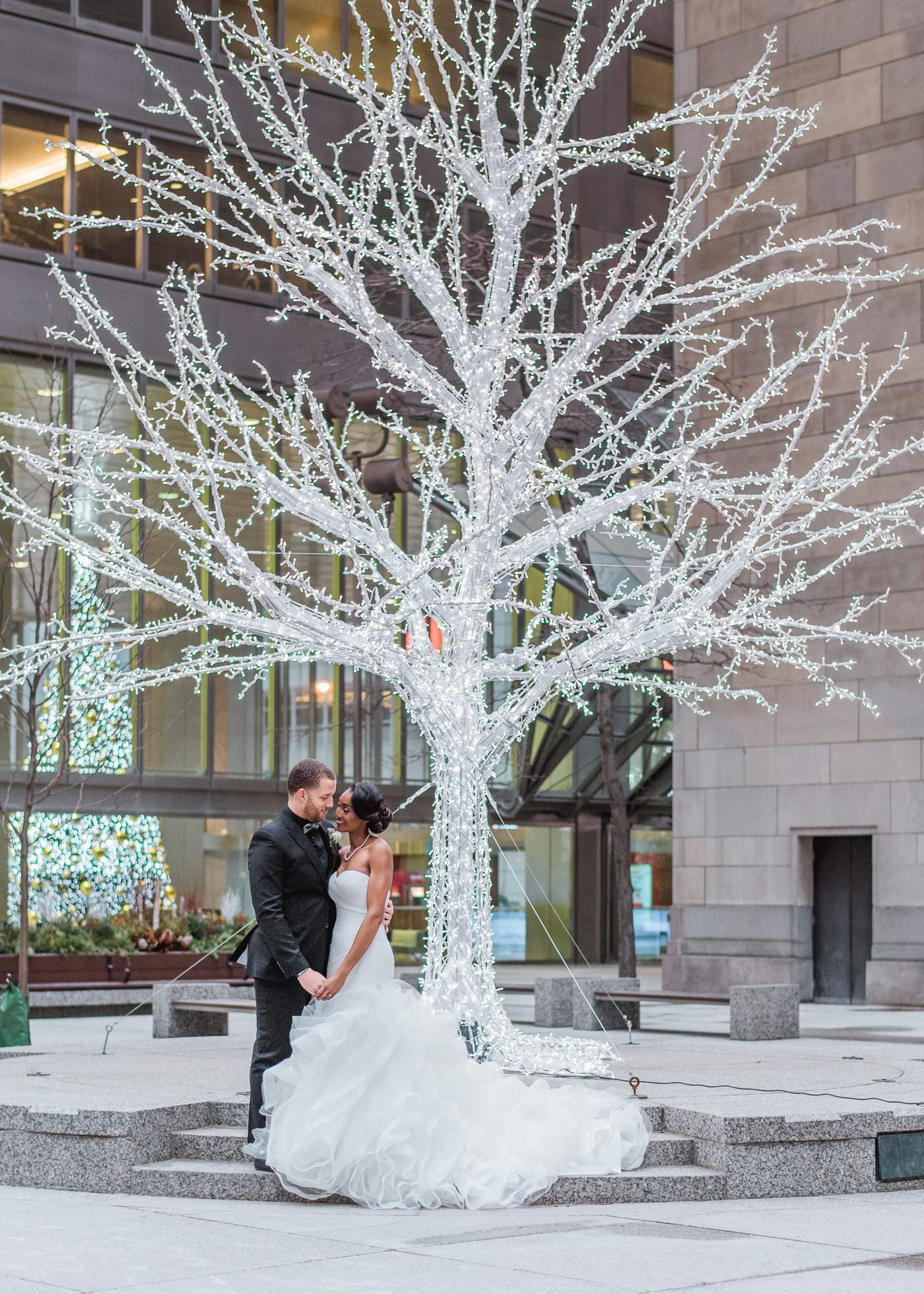 Couple posing under a christmas tree at One King West Wedding in Toronto